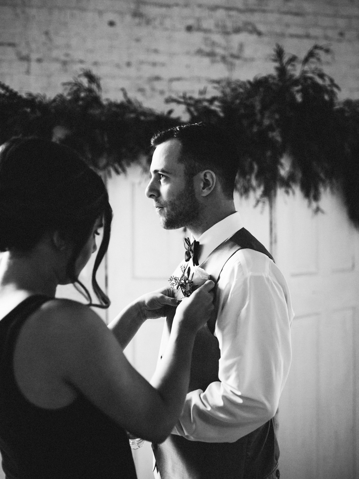 A groom has his boutonniere pinned on at The Brick wedding venue