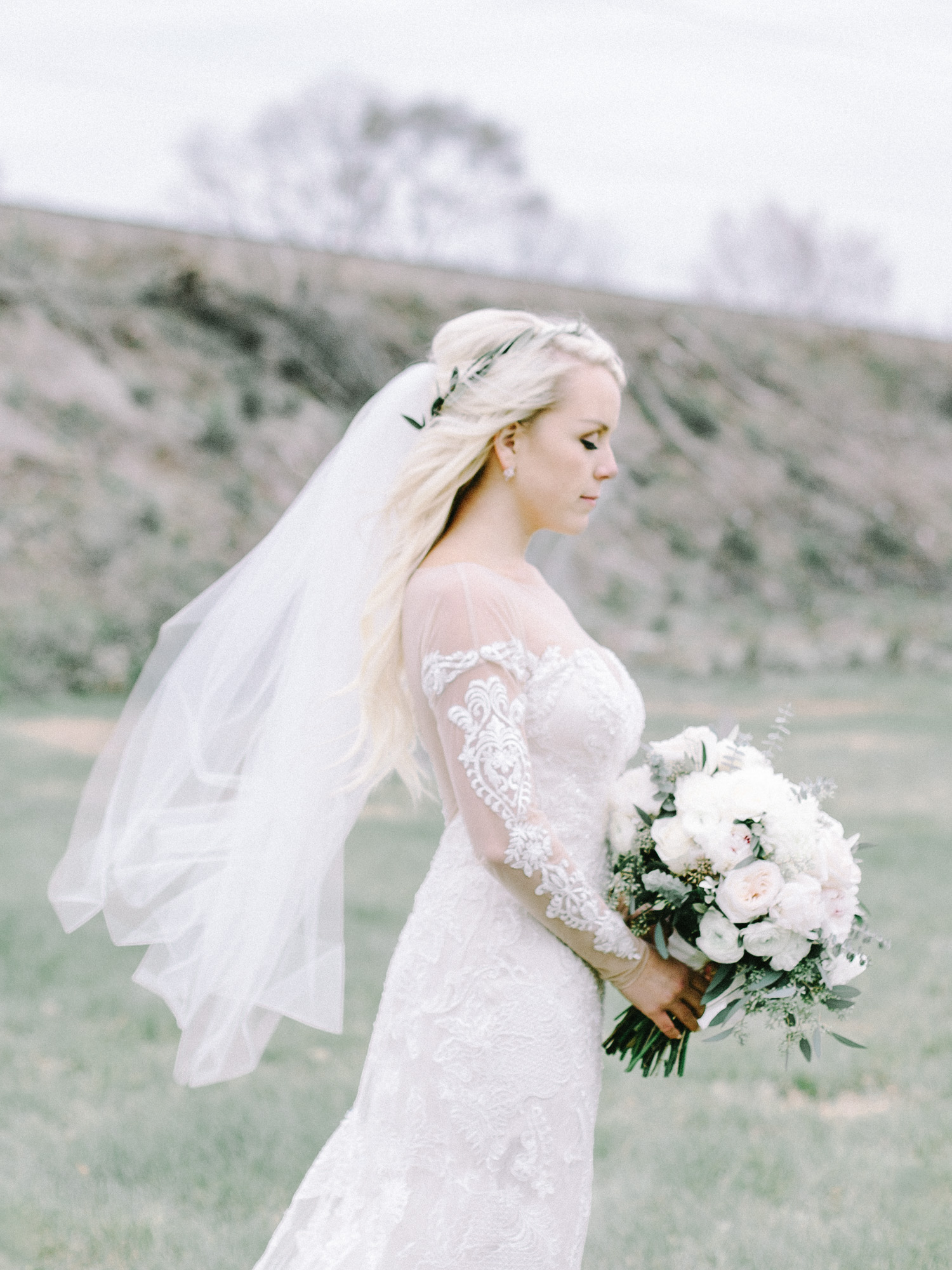 A bride's mid-length veil blows in the wind as she holds her bouquet at her Indiana wedding venue, The Brick