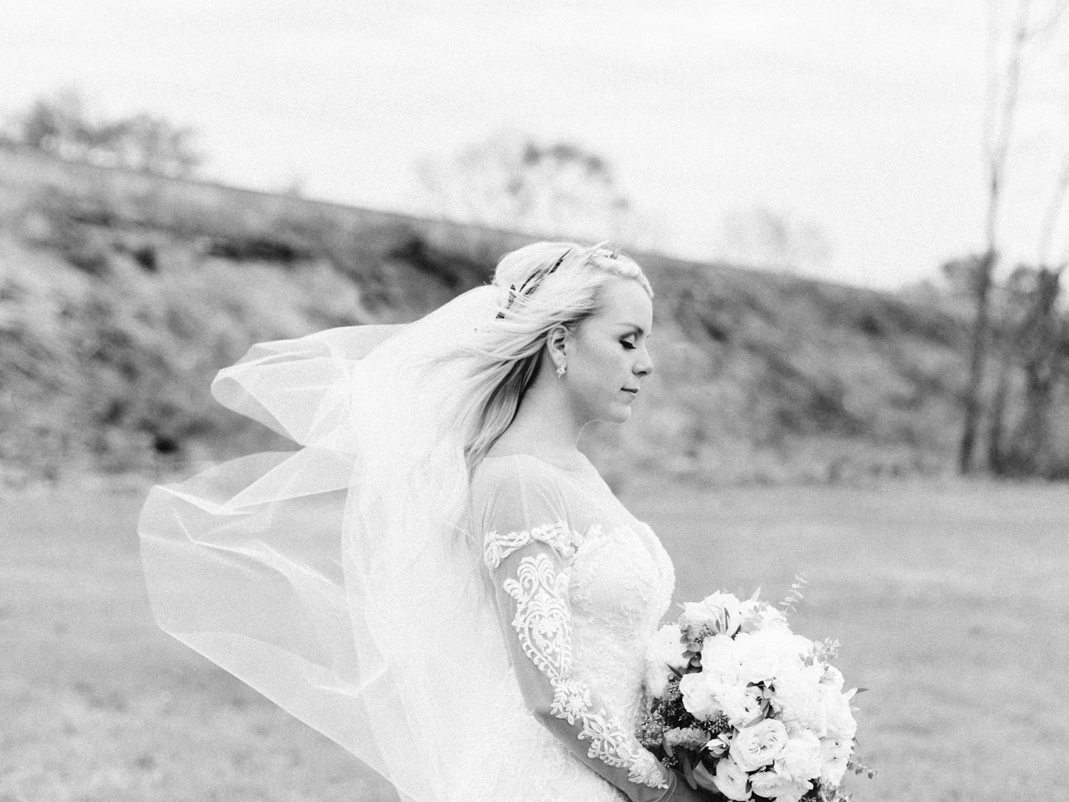 A bride closes her eyes and feels the wind blowing her veil at her Indiana wedding at The Brick