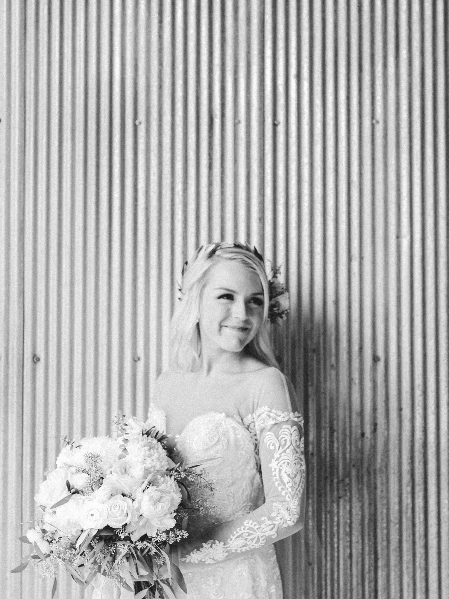 a bride smiles while holding her bouquet at her industrial wedding venue, The Brick in South Bend