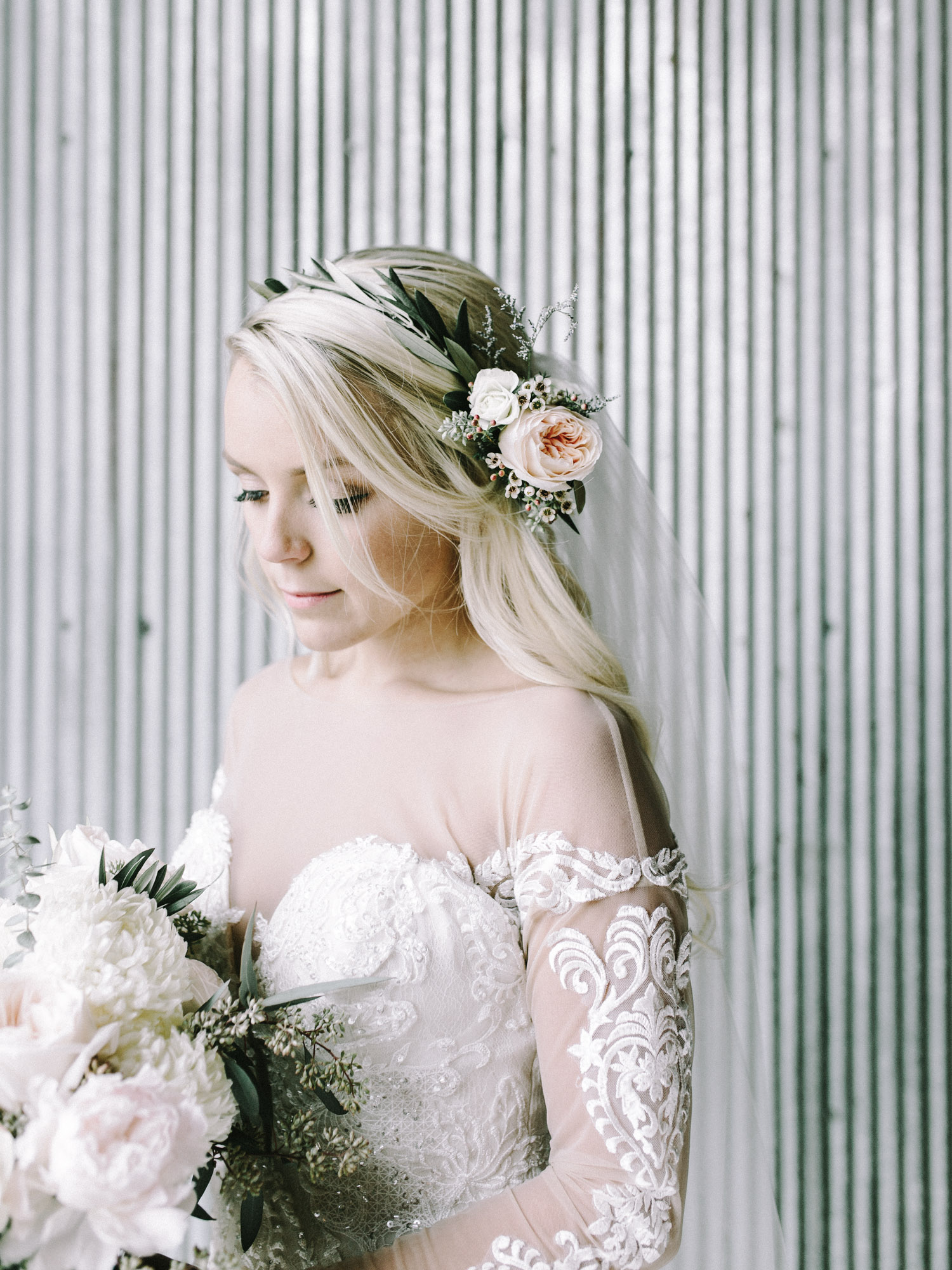 A bride in an olive flower crown looks down at her bouquet in her industrial wedding venue space, The Brick in Indiana