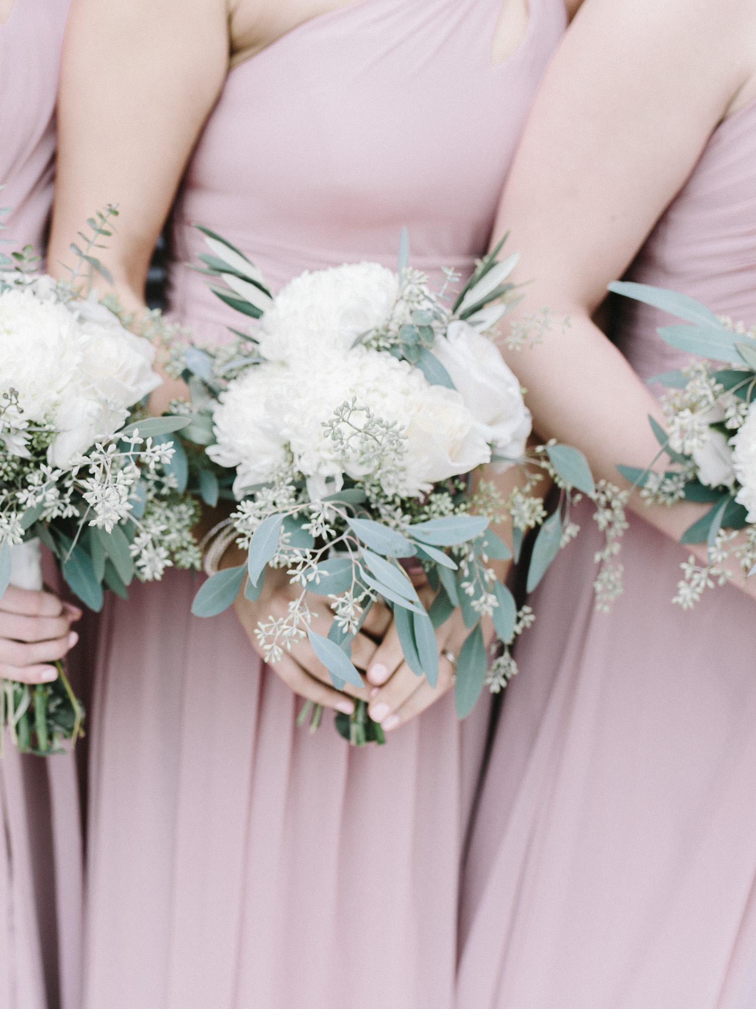 Bridesmaids in romantic blush dresses hold bouquets of white flowers and eucalyptus by film wedding photographer Christina Harrison