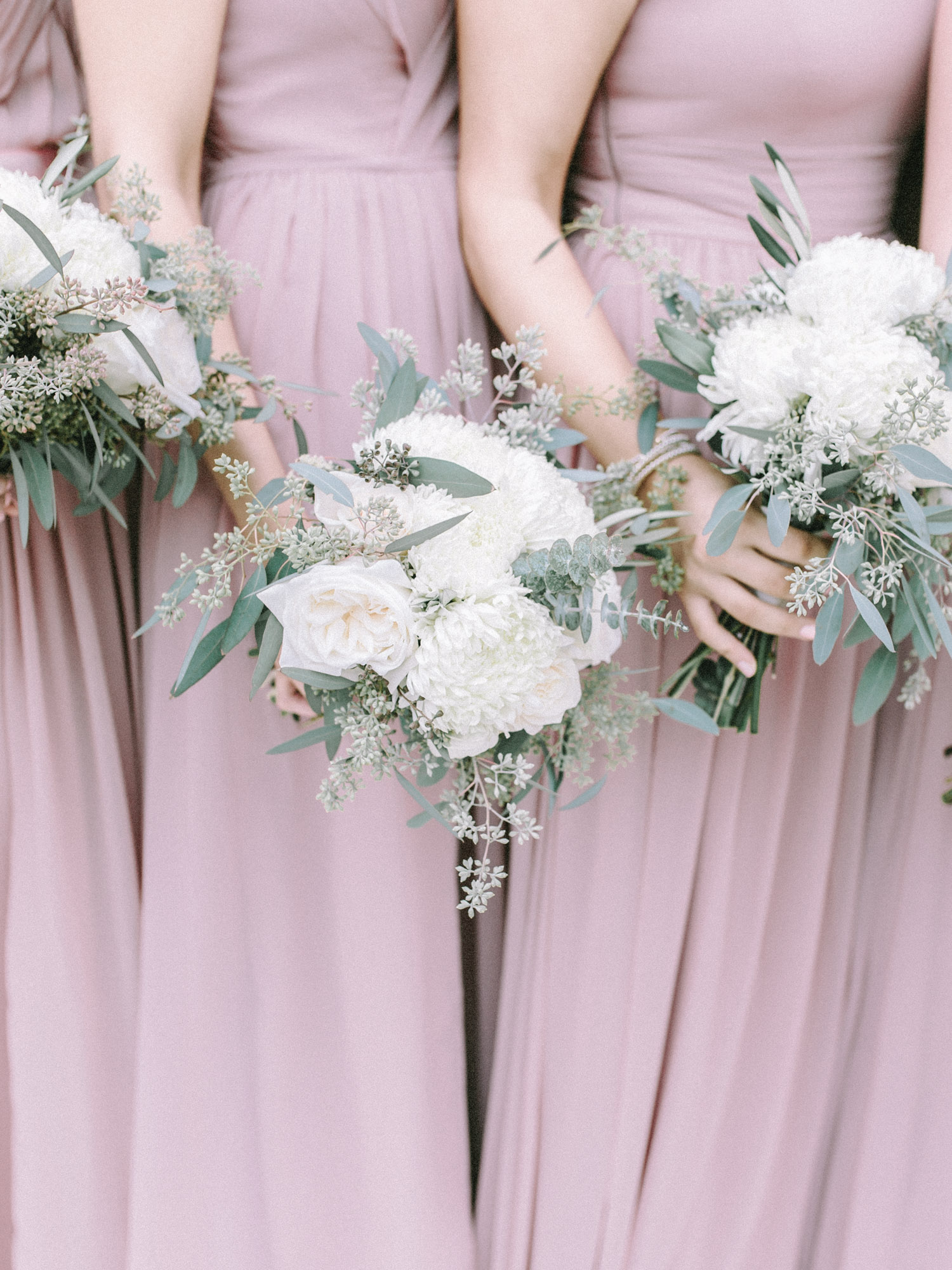 Bridesmaids in romantic blush gowns hold bouquets with big white flowers and seeded eucalyptus