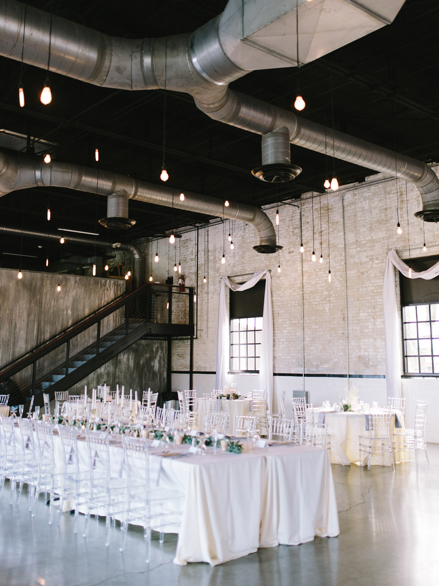 An industrial and romantic wedding reception design with hanging Edison bulbs and ethereal white and blush tables at The Brick by Christina Harrison Photography