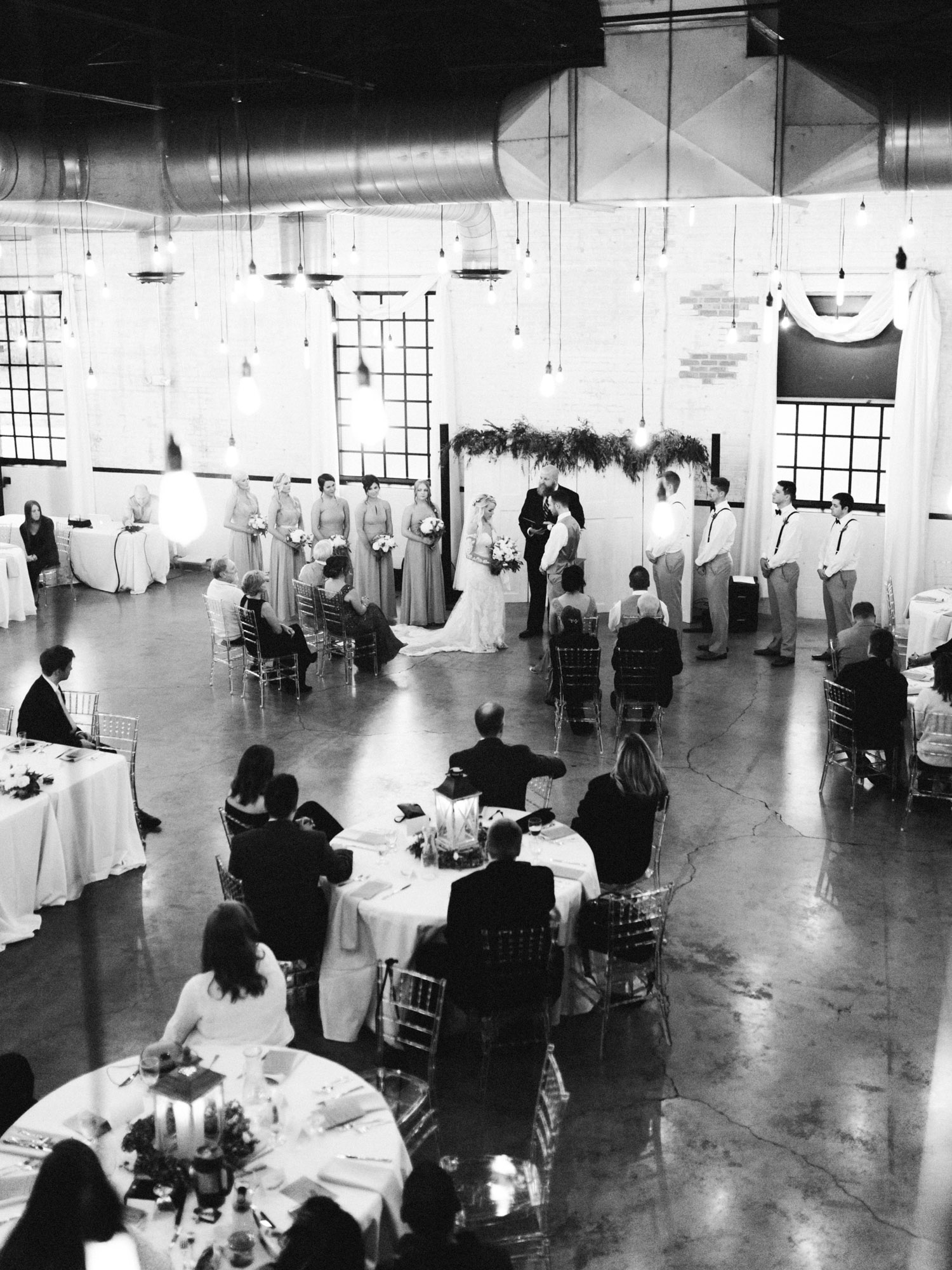 An intimate wedding ceremony in an industrial wedding venue with hanging Edison bulbs, The Brick in South Bend, Indiana