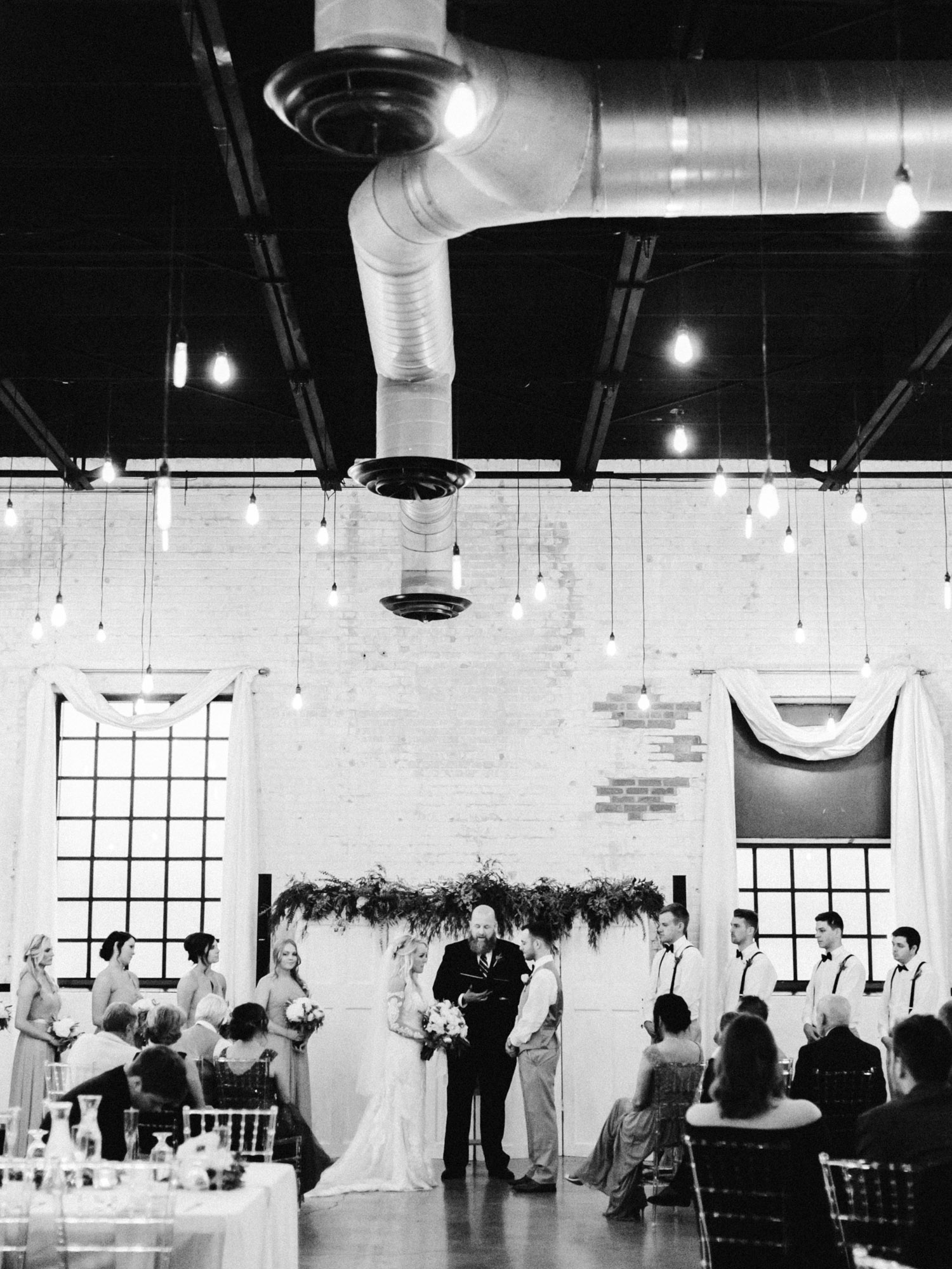 A wedding ceremony at The Brick in South Bend, a light industrial wedding venue with hanging Edison light bulbs in Indiana