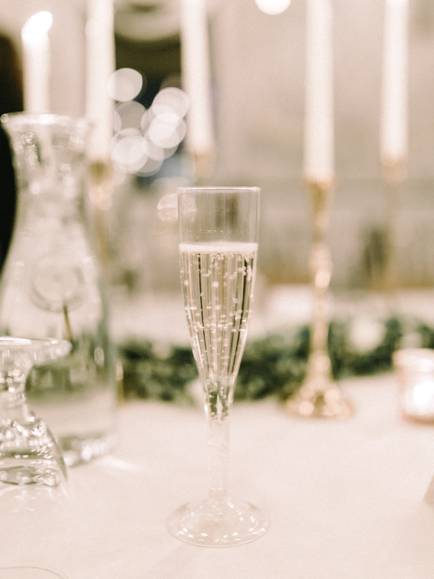 A bubbly glass of champagne fizzes on a candlelit reception table at a reception at The Brick wedding venue in Indiana