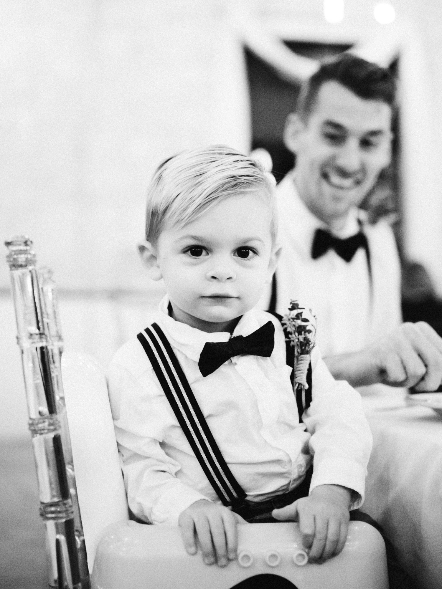 A cute toddler ring bearer in suspenders looks at the camera at a wedding reception at The Brick in South Bend, Indiana