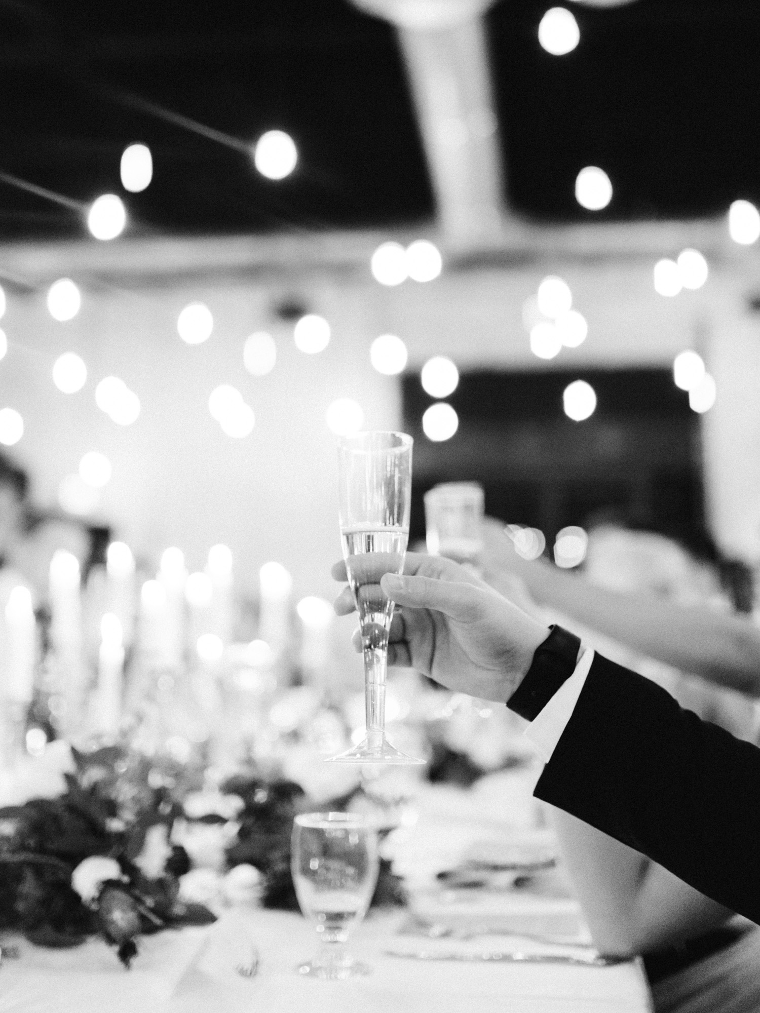A groomsman raises a glass during the champagne toast at a wedding reception at The Brick in South Bend, Indiana