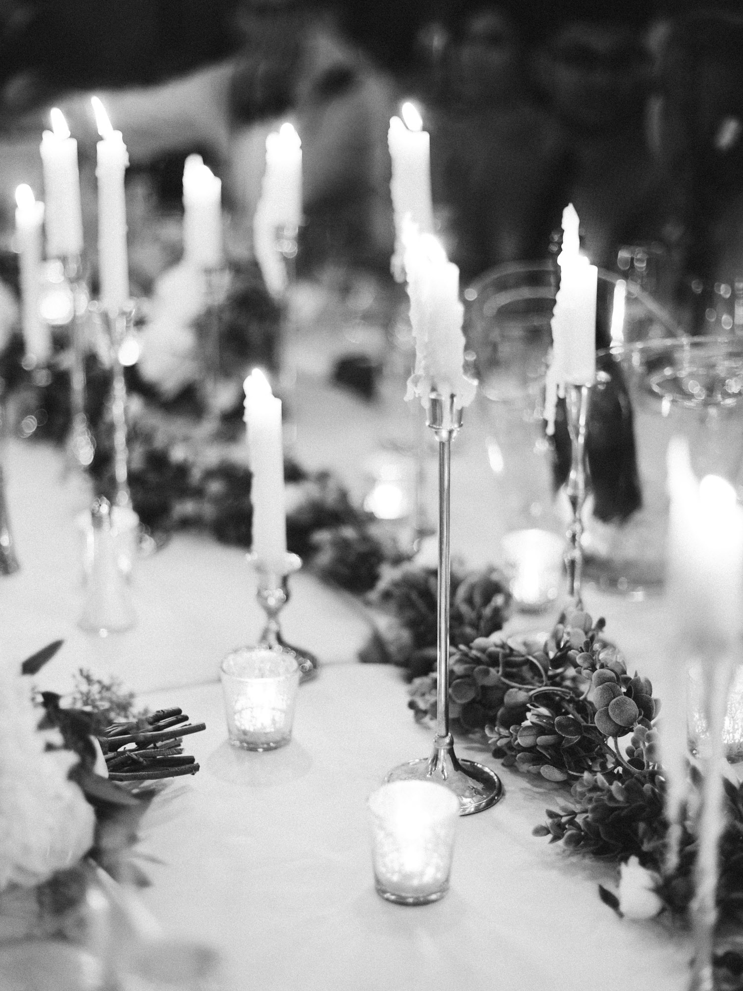 Romantic black and white film wedding photography of taper candles dripping wax on a reception table at The Brick in Indiana