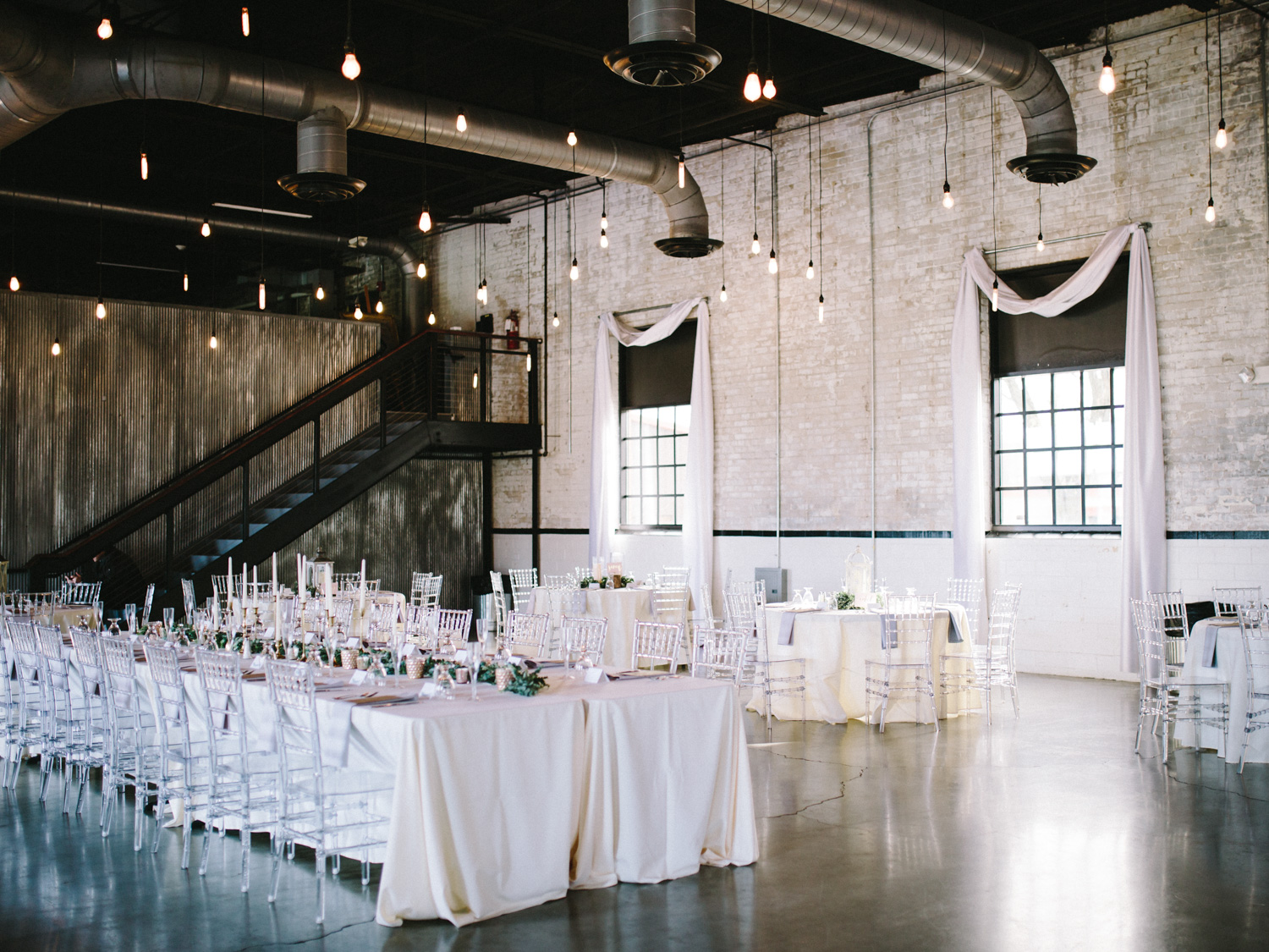 A romantic and ethereal blush and white wedding reception with hanging Edison bulbs at The Brick in Indiana