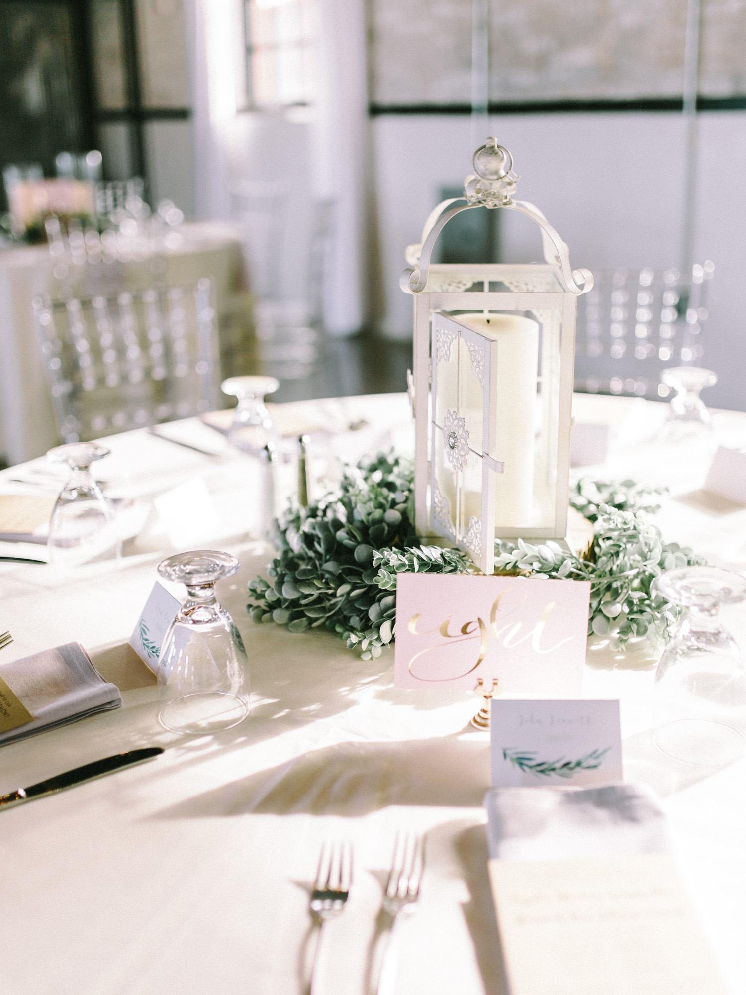 Sunlight falls on an ethereal wedding reception table with a white lantern centerpiece, greenery, and calligraphy table number in South Bend, Indiana