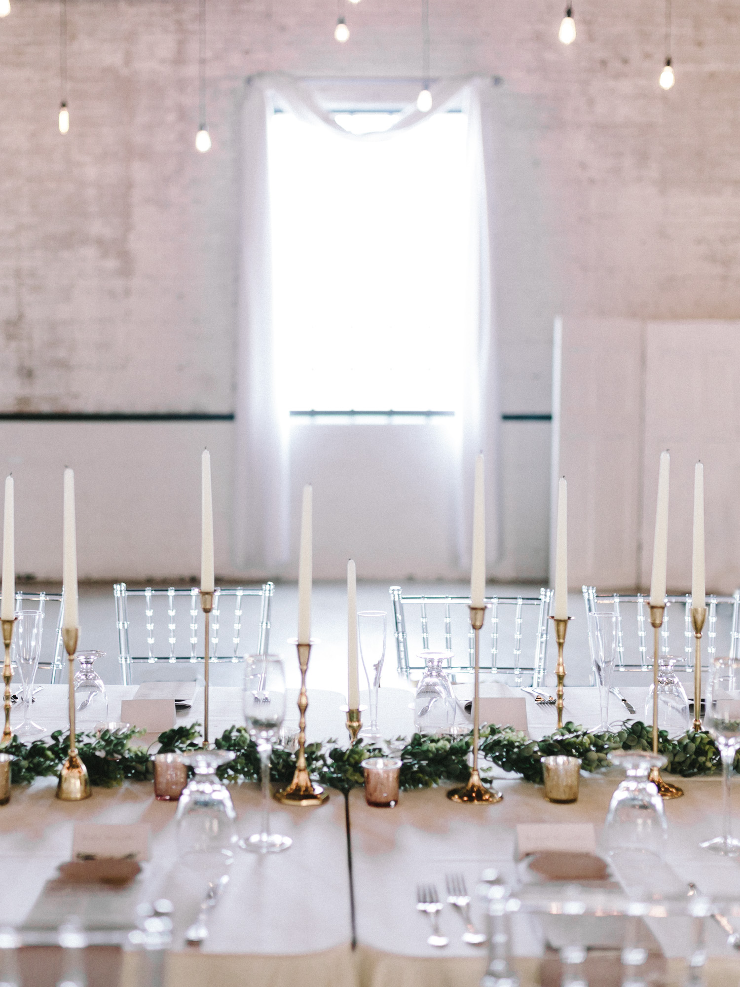 Romantic and ethereal blush, white, and gold reception details with a greenery runner and pillar candles at The Brick in South Bend by wedding photographer Christina Harrison
