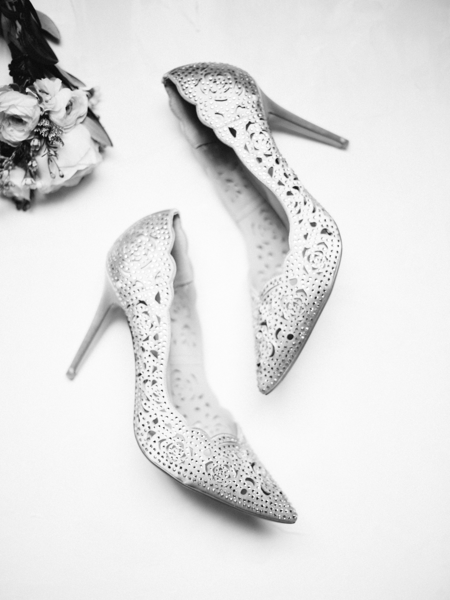 lace wedding stilettos with cutout detail rest on a white background