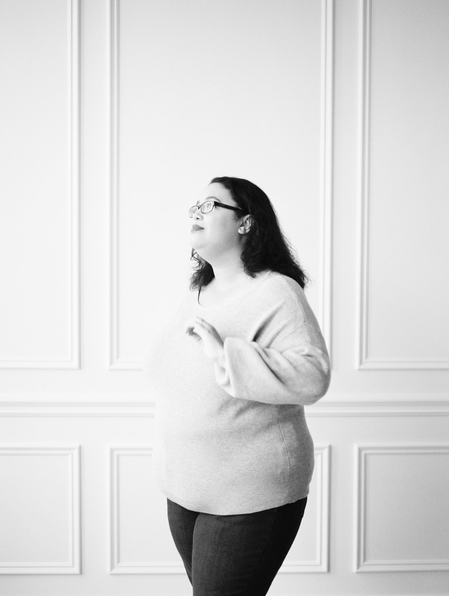 A creative business owner in a clean white space with molding at her brand photoshoot on film in Detroit, Michigan