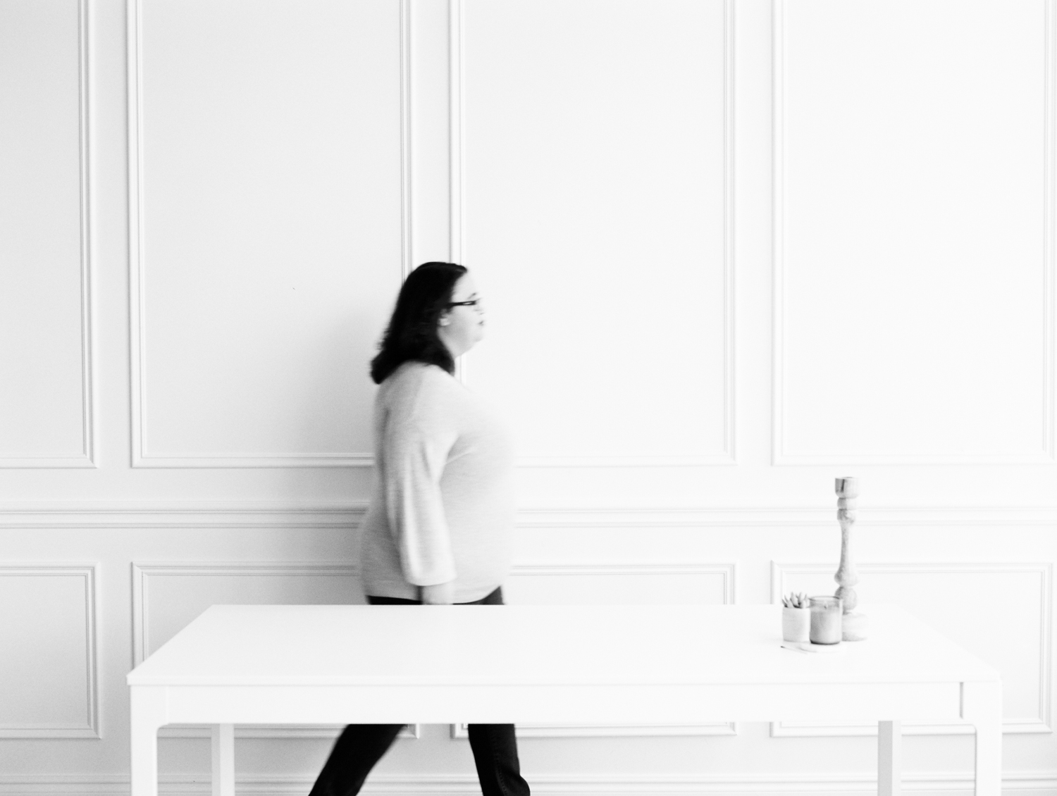 Motion blur is caught as creative business owner Stefani Jessica walks behind a white desk at Tribe Detroit during her brand photoshoot on film