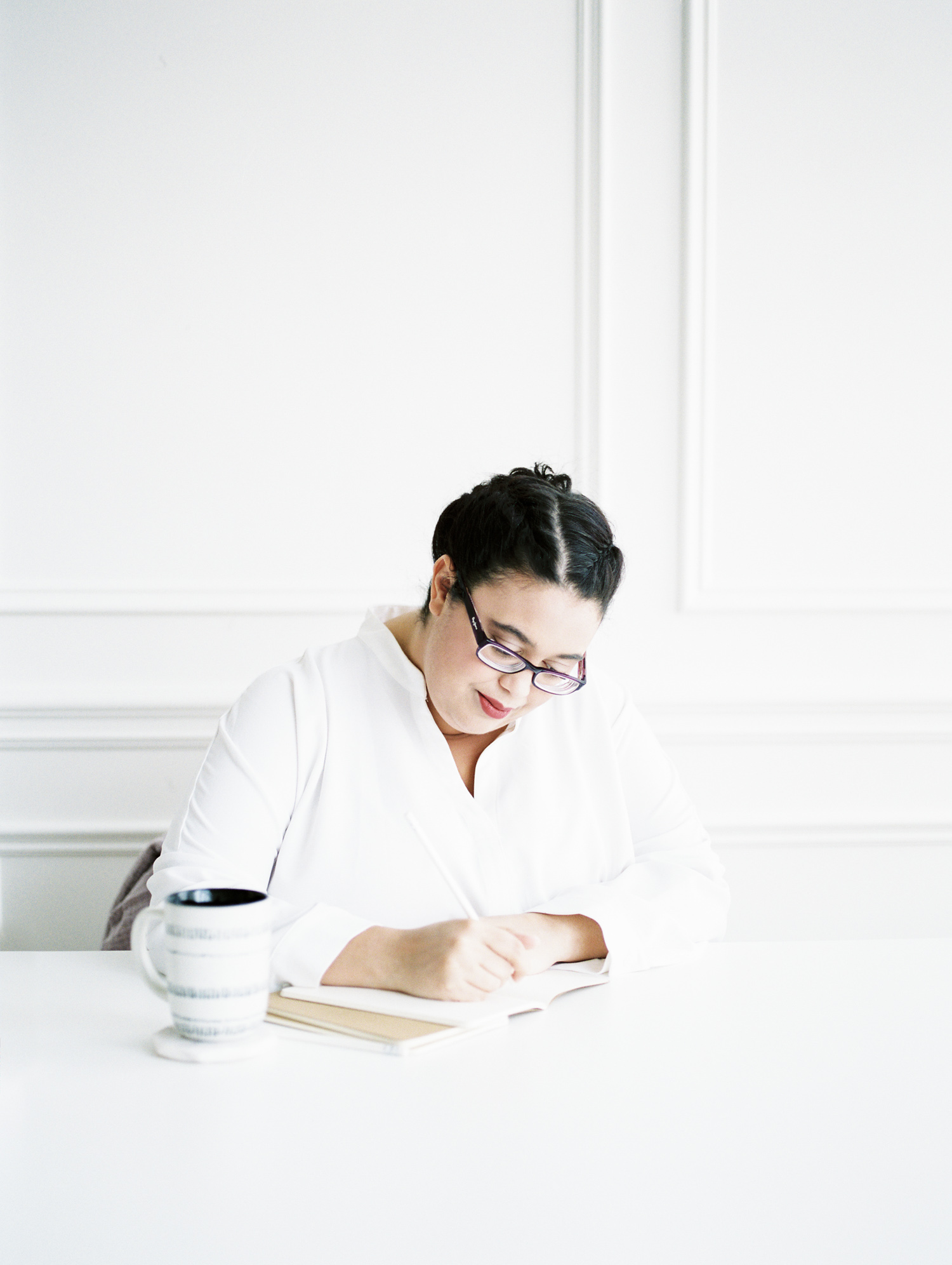 Stefani of Stefani Jessica Studio writes at a white desk in a clean, white space in Detroit, Michigan at her brand photoshoot