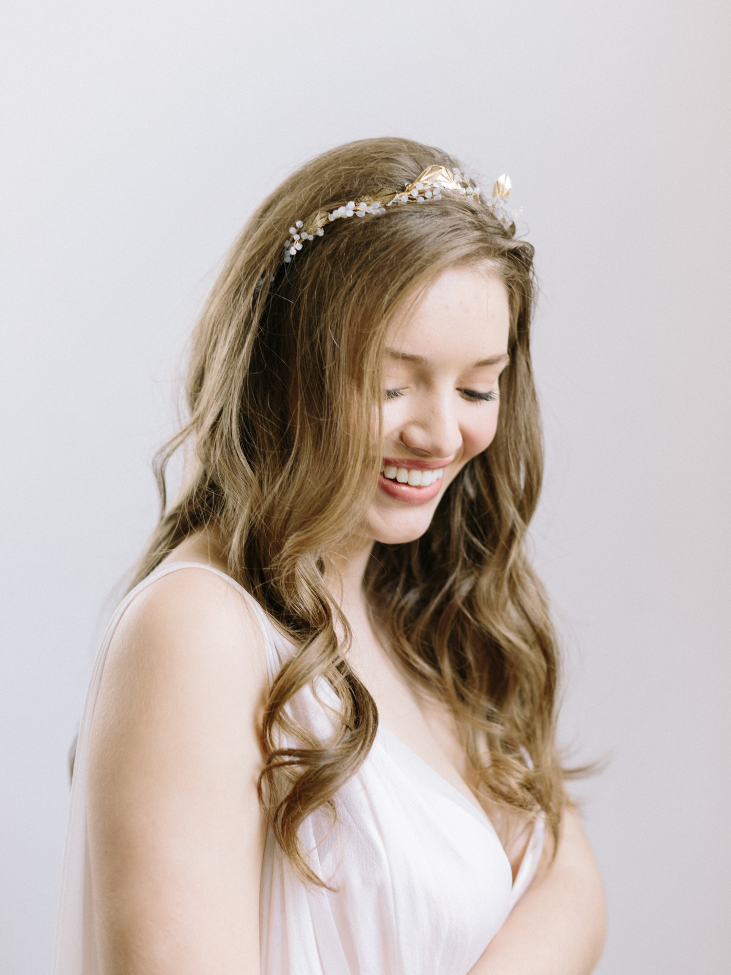 A bride in a gold vine headpiece with her hair down and curled laughs while looking down