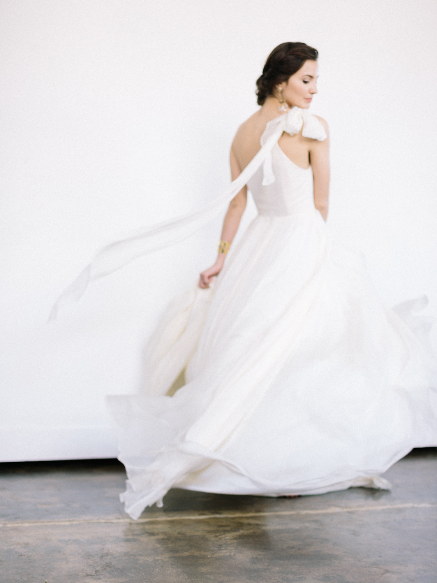 A bride in a silk Leanne Marshall gown twirls, creating billowing movement with layers of silk