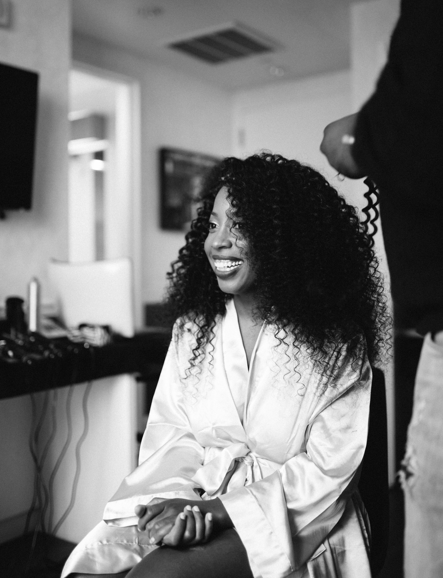 A black bride with full, curly hair laughs while getting ready for her Brooklyn Winery Wedding