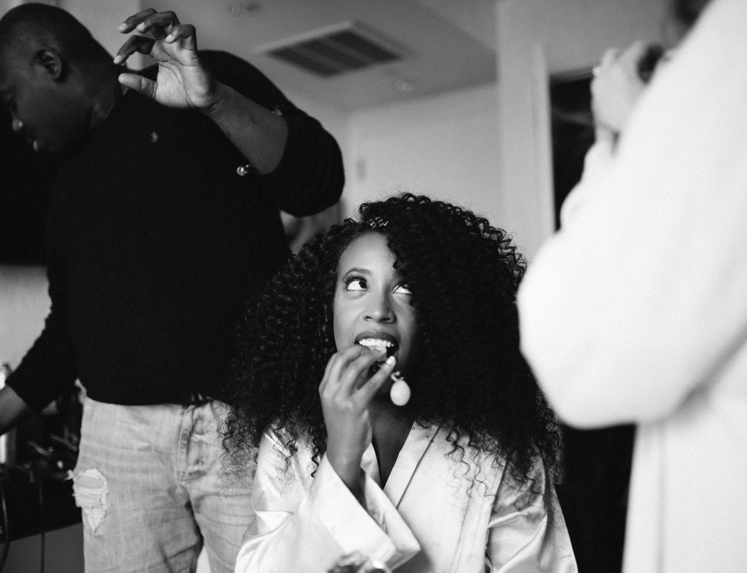 A bride is caught snacking on grapes while stylists do her hair and makeup while getting ready for her Brooklyn Winery wedding