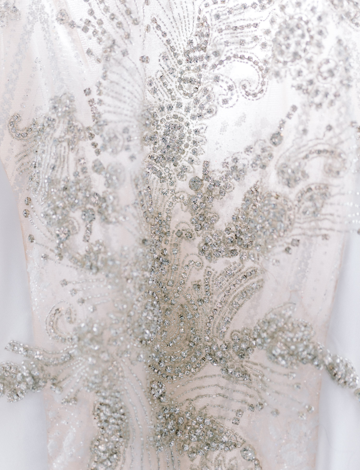 Close detail of a wedding dress with a sheer bodice and intricate beading and crystal detail for a same-sex New York City wedding