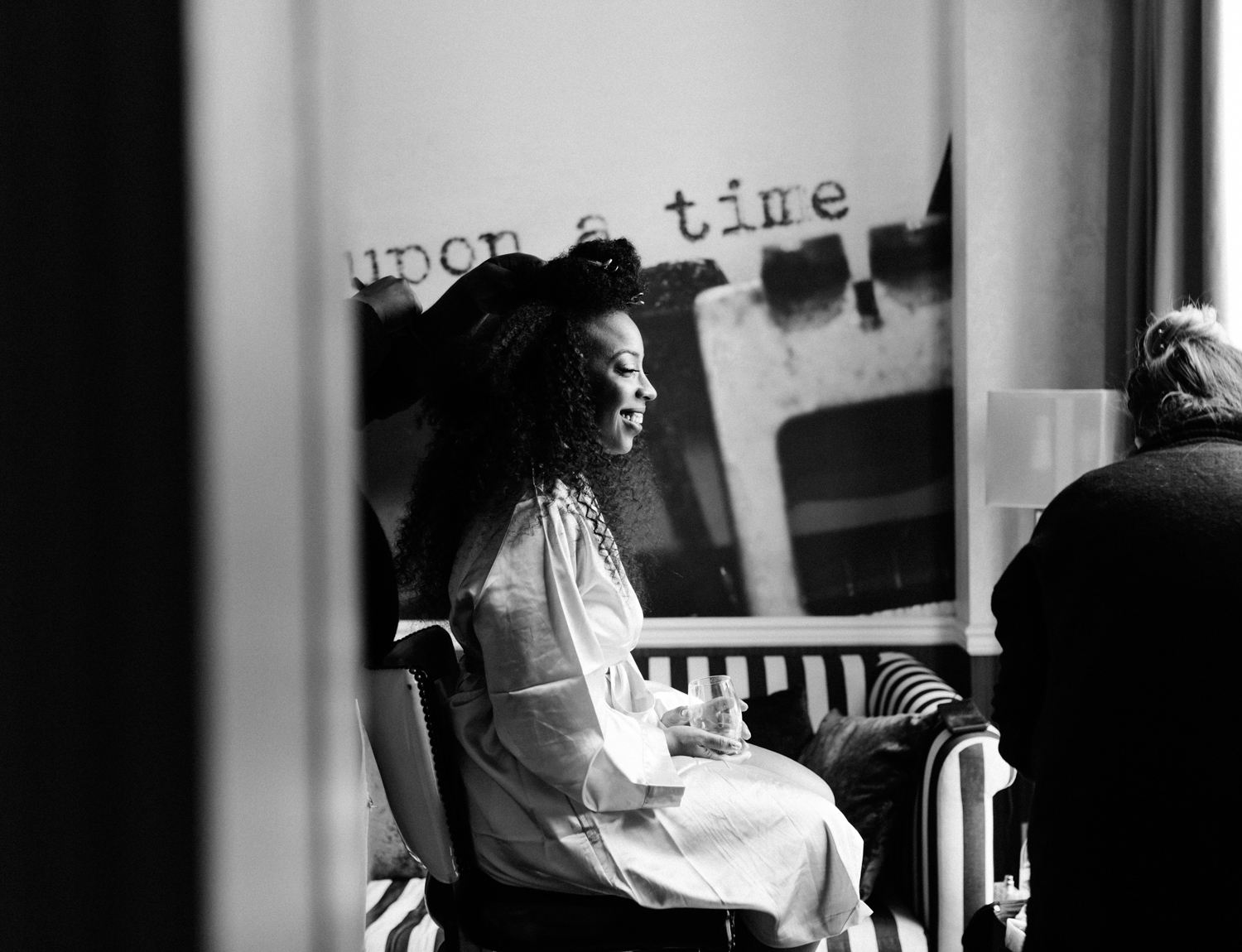 A black bride laughs while having her hair done for her same-sex wedding in Brooklyn, New York