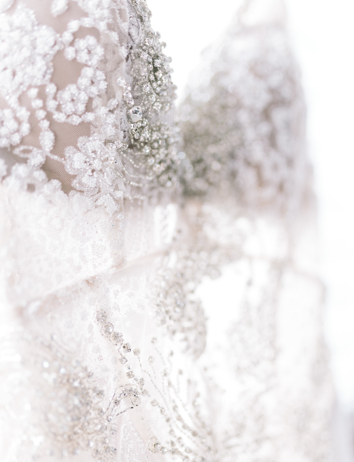 close up detail of a wedding dress with a sheer bodice and intricate beading and crystal detail in New York City