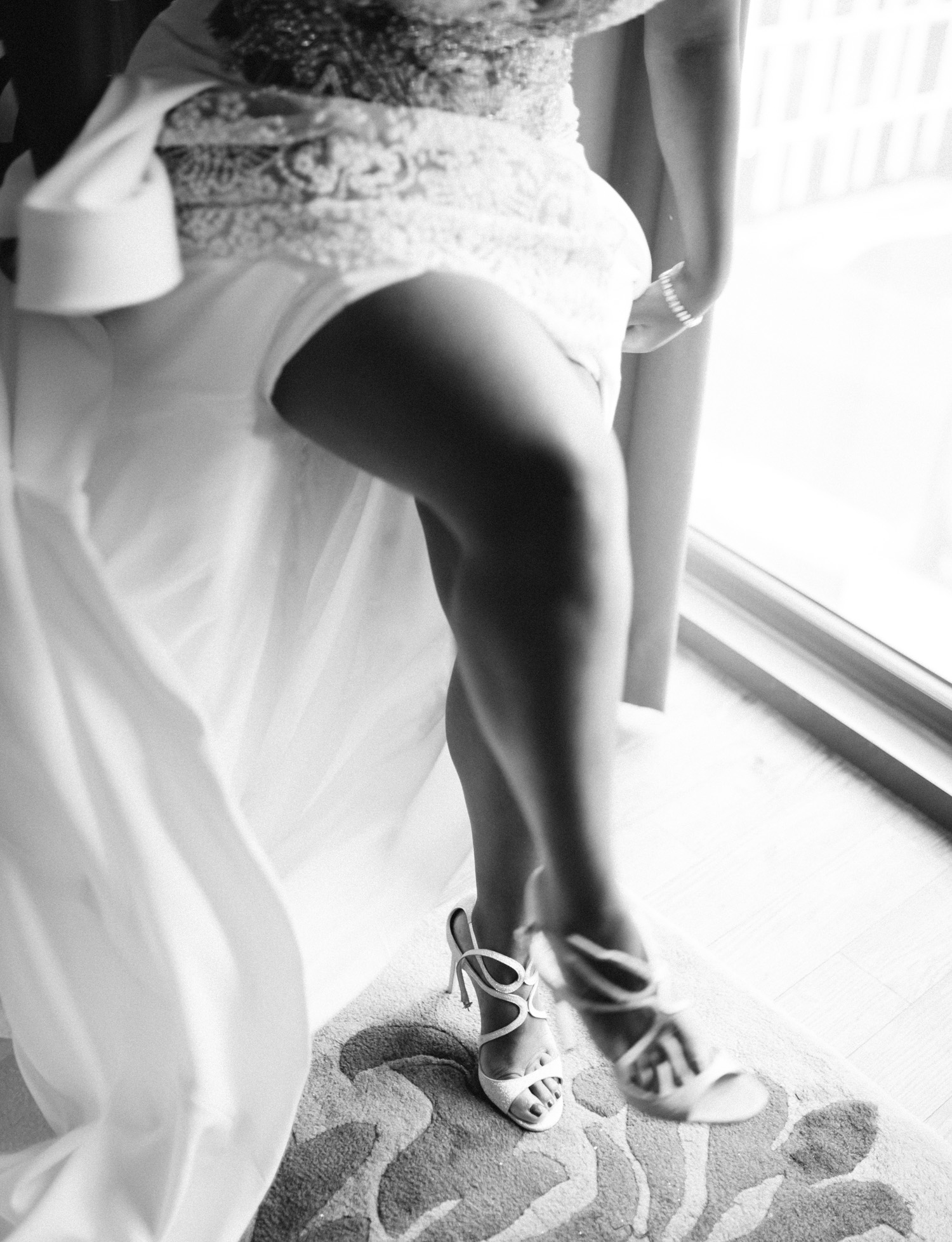 A black bride fastens her Jimmy Choo wedding shoes in a Brooklyn, New York hotel room