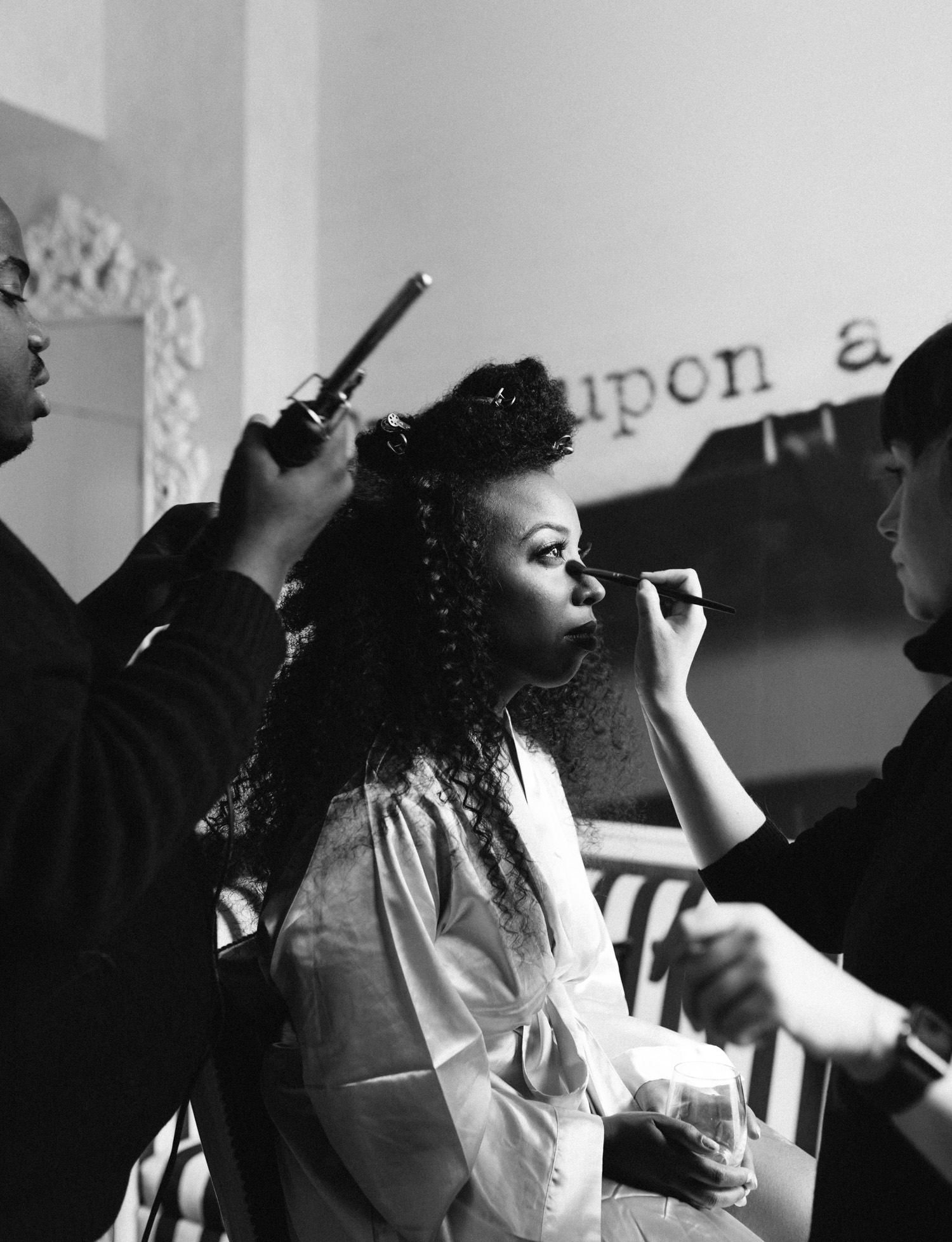 A black bride gazes upward while having her hair and makeup done in preparation for her Brooklyn Winery wedding in New York City