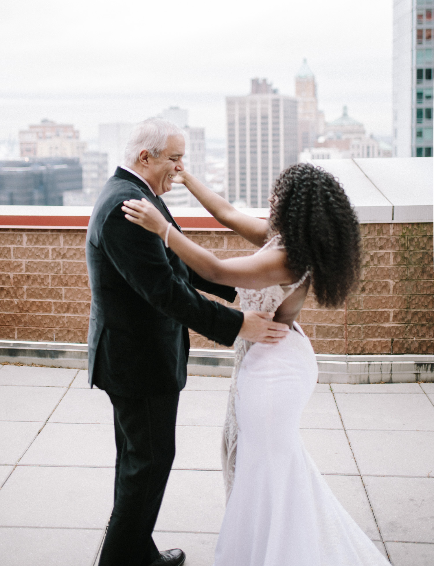 A black bride shares a first look moment with her father on a rooftop in New York City