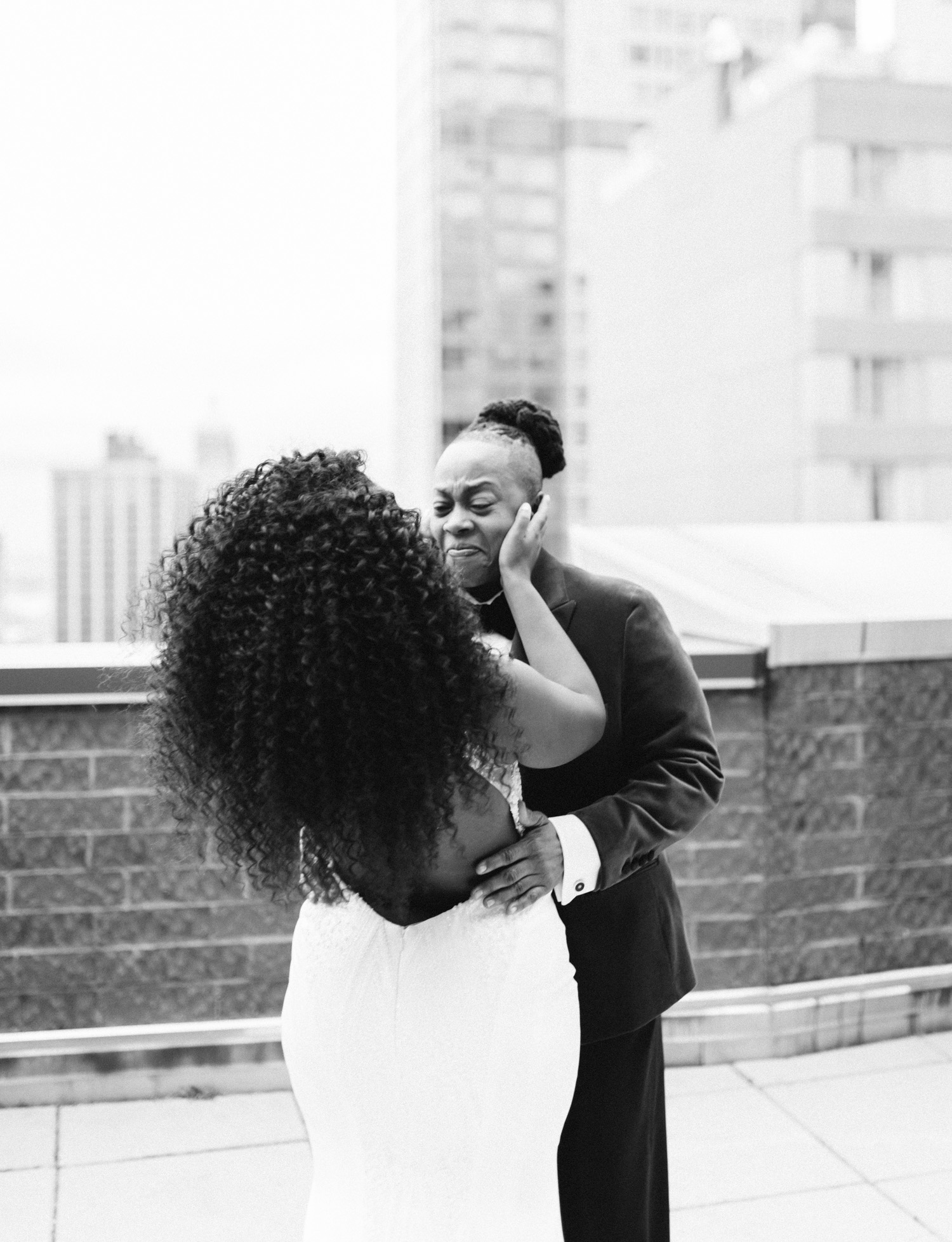 A black same sex couple embraces while seeing each other for the first time on a New York City rooftop before their Brooklyn Winery wedding