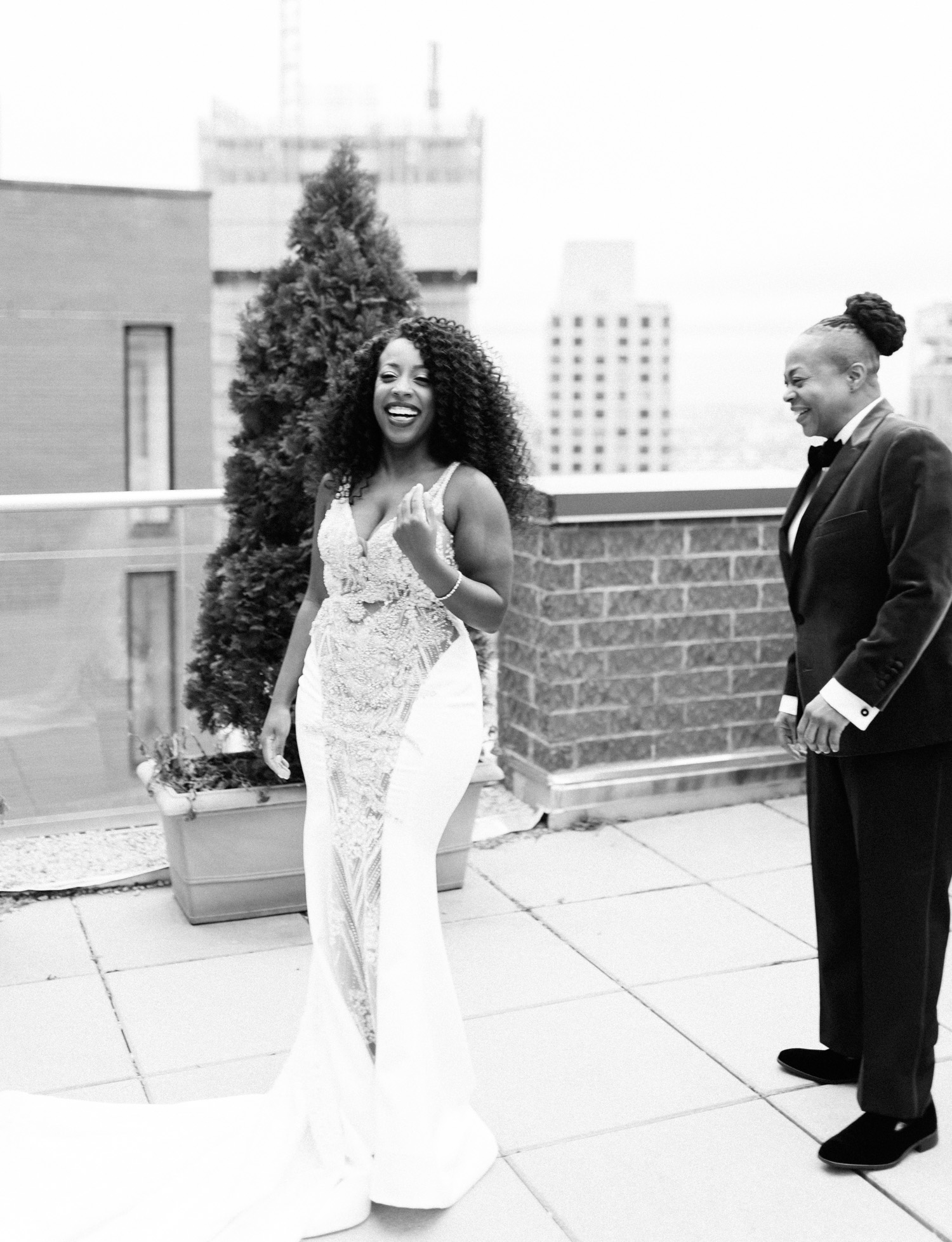 A black same sex wedding couple laughs together during their first look on a New York City rooftop before their Brooklyn Winery wedding ceremony