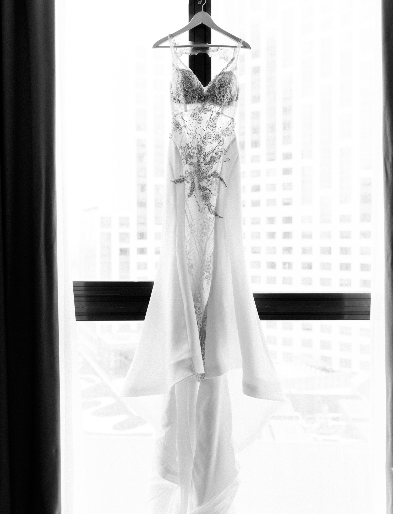 A fitted wedding dress with intricate beading and crystal detail on a sheer bodice hangs in a window among skyscrapers in Brooklyn, New York