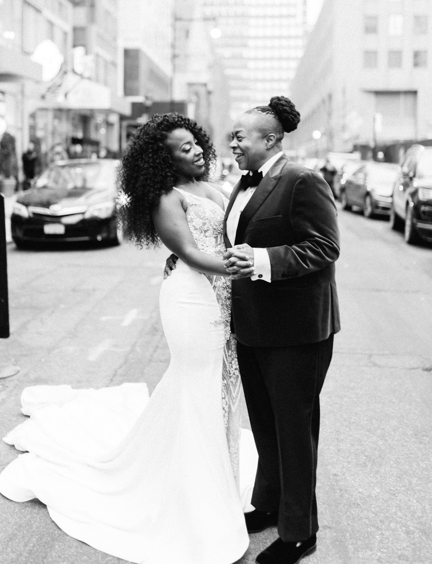 A black same sex couple dances in the streets of New York City on their wedding day in Brooklyn