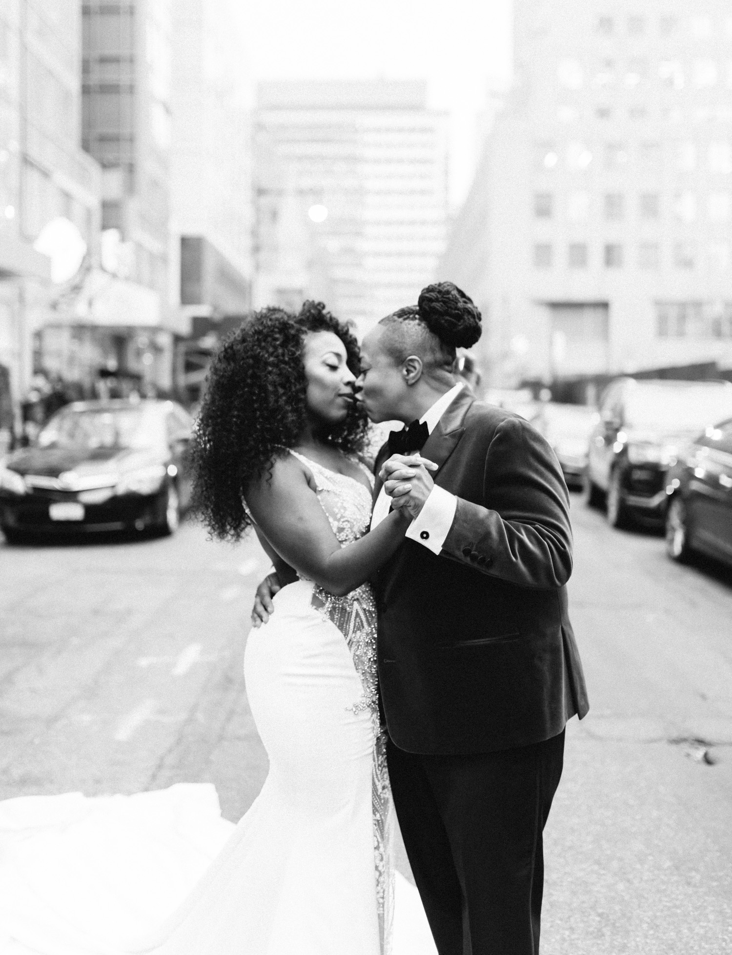A black same sex couple kisses in the streets of New York City on their wedding day in Brooklyn