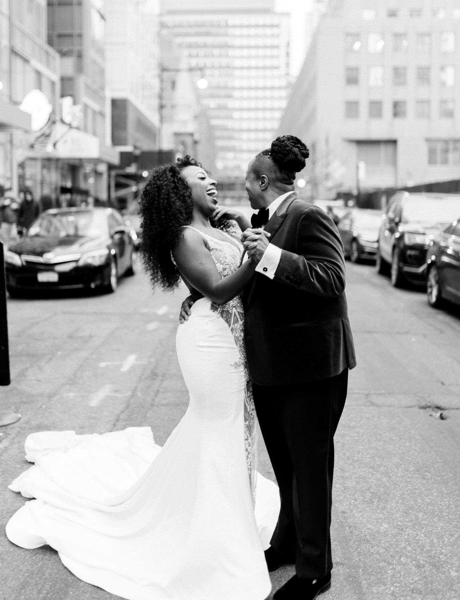 Before their Brooklyn Winery wedding, a black lesbian wedding couple laugh together in the streets of New York City