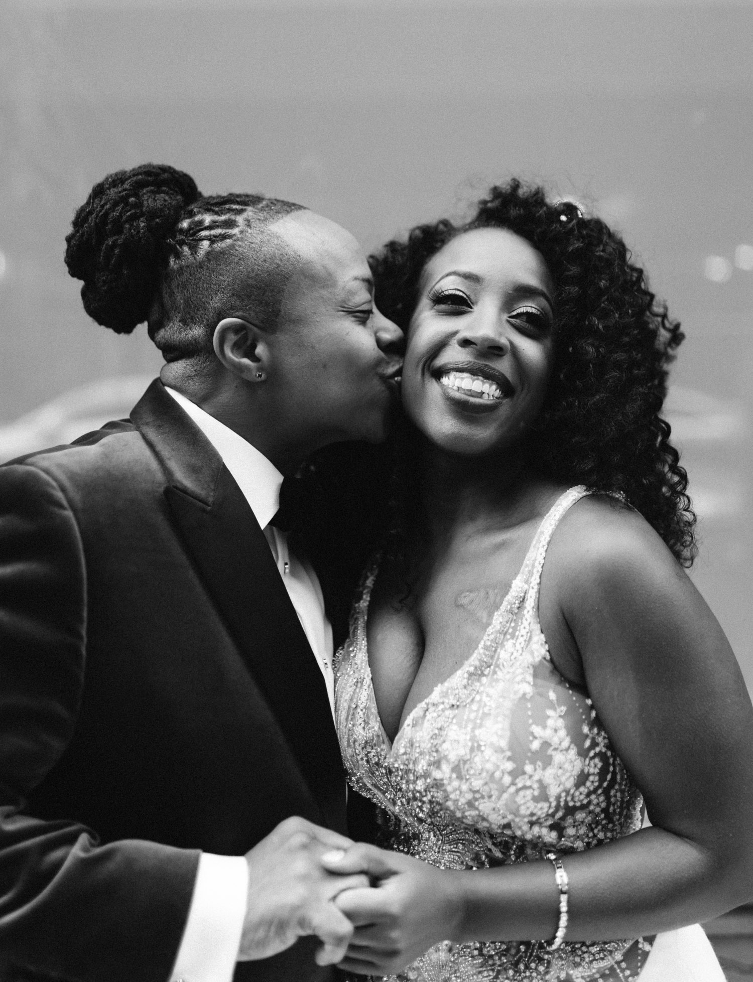 A black lesbian wedding couple embrace on the streets of New York City before their Brooklyn Winery wedding ceremony
