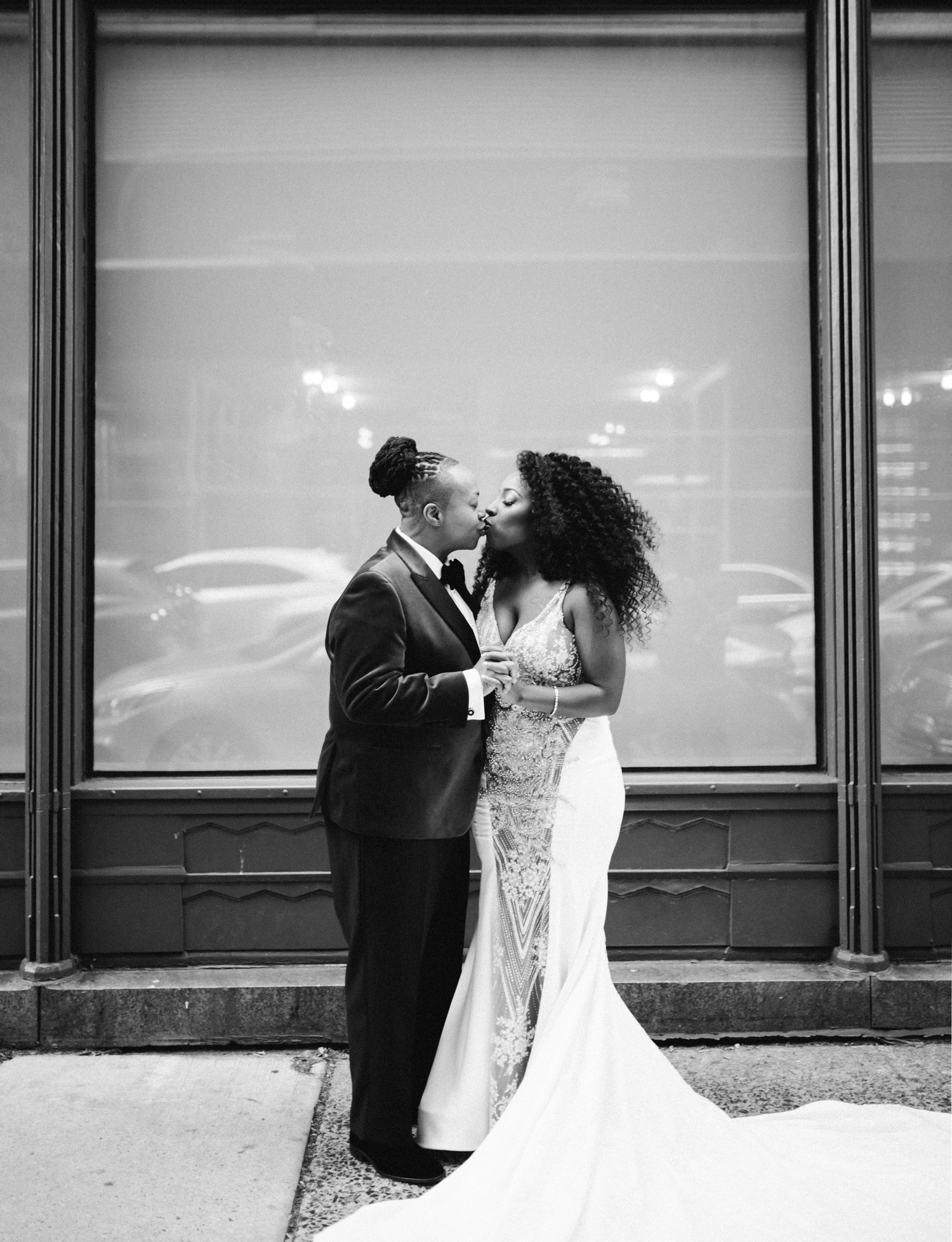 A black same sex wedding couple kisses on the streets of New York City in winter before their Brooklyn Winery wedding ceremony