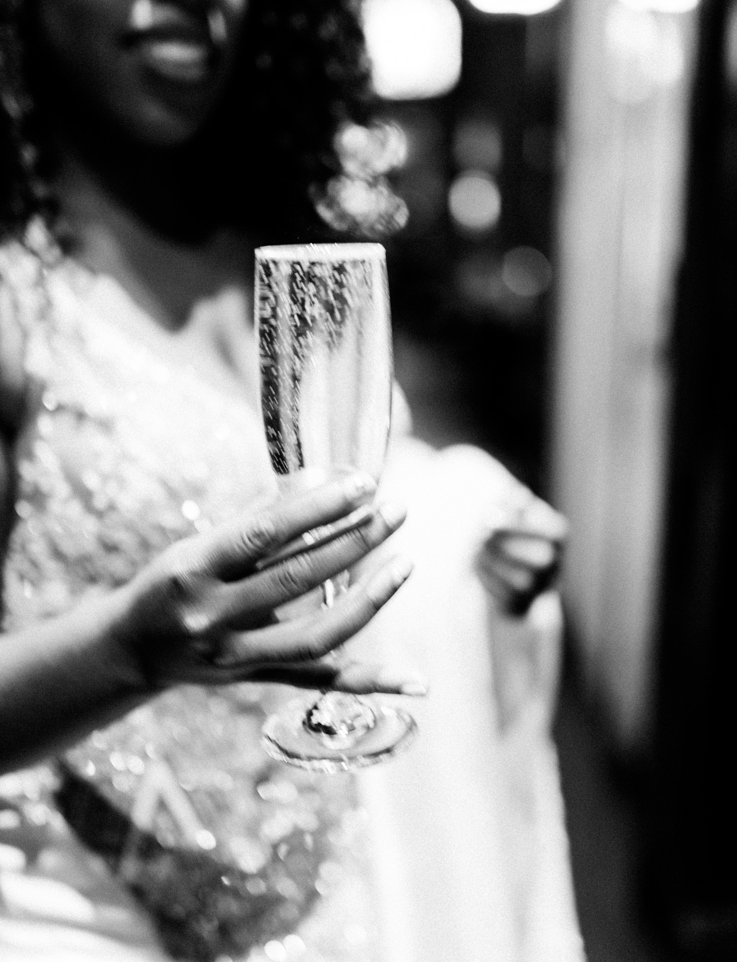 A bride holds a bubbly glass of champagne on her wedding day in Brooklyn, New York