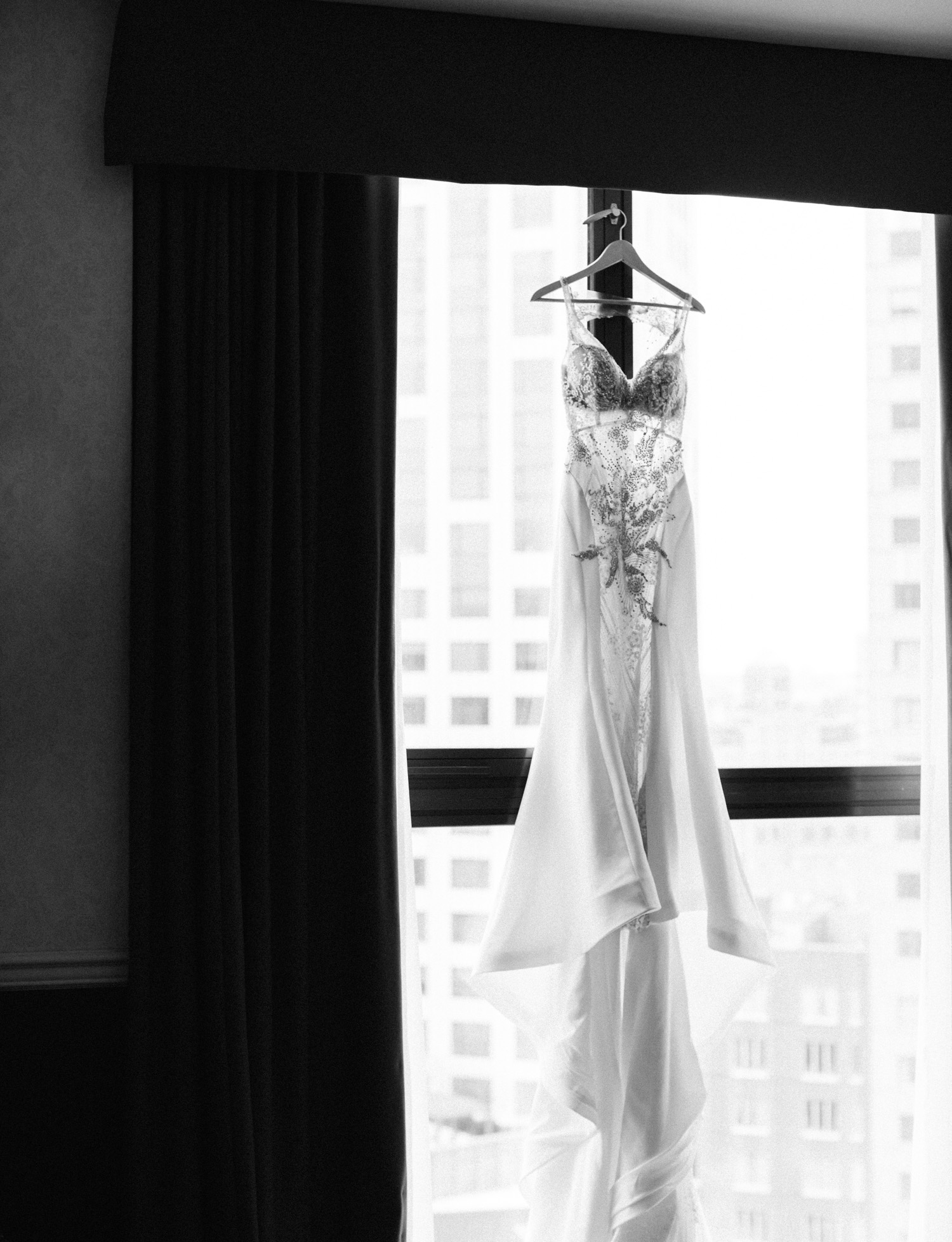 A fitted wedding dress with sheer bodice and intricate beading detail hangs in a Brooklyn, New York window