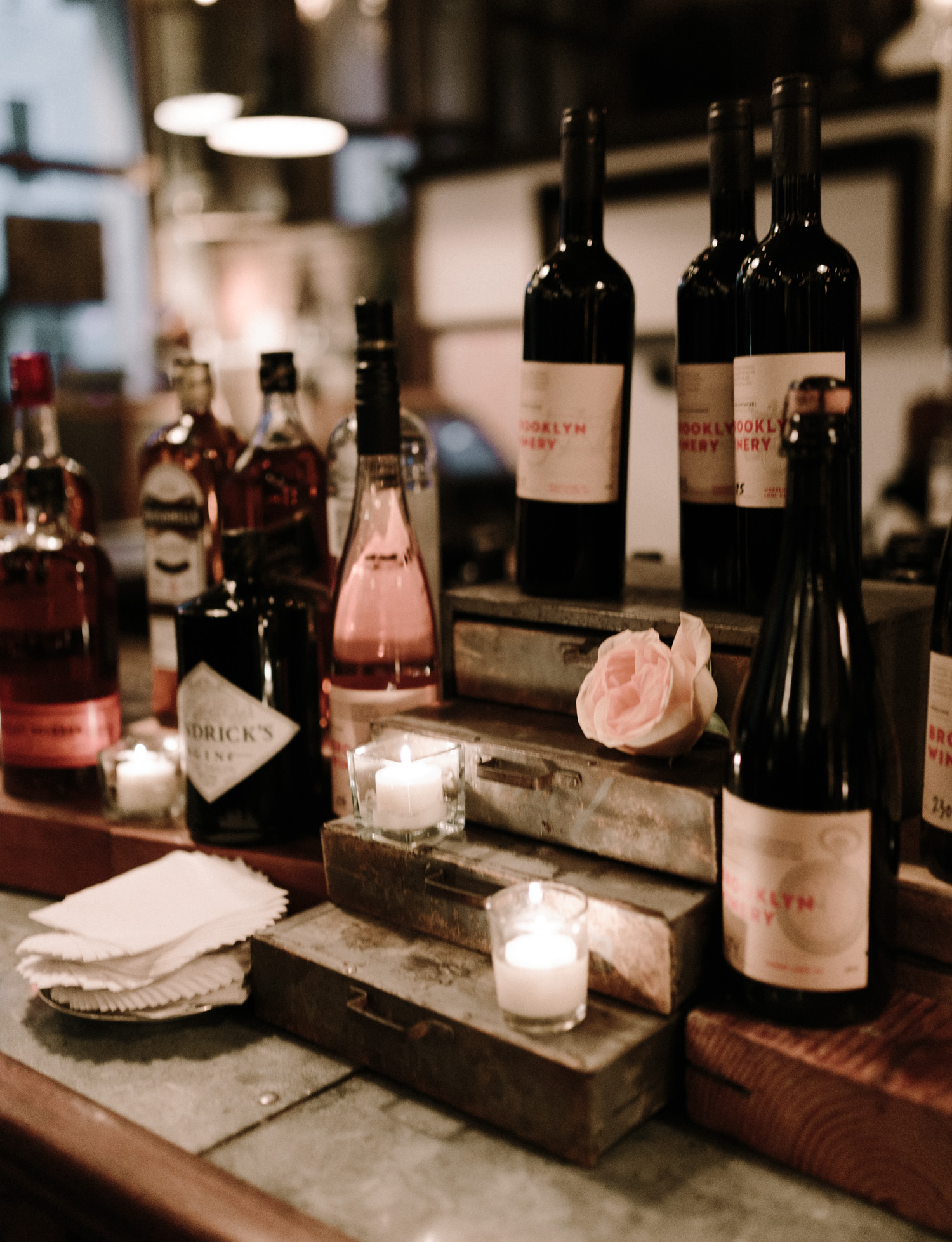 A candlelit display with bottles of wine and flowers for a same sex winter wedding at Brooklyn Winery in Brooklyn, New York City