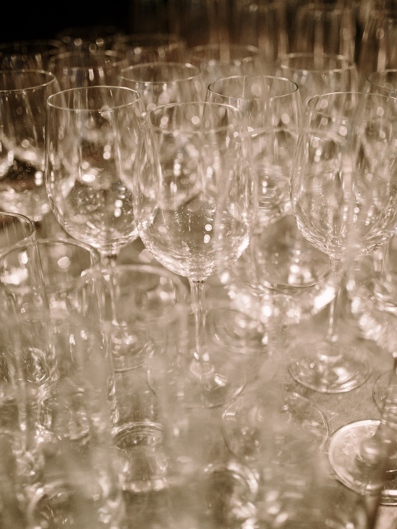 Empty wine glasses with a golden glow rest before a wedding reception at Brooklyn Winery in New York City