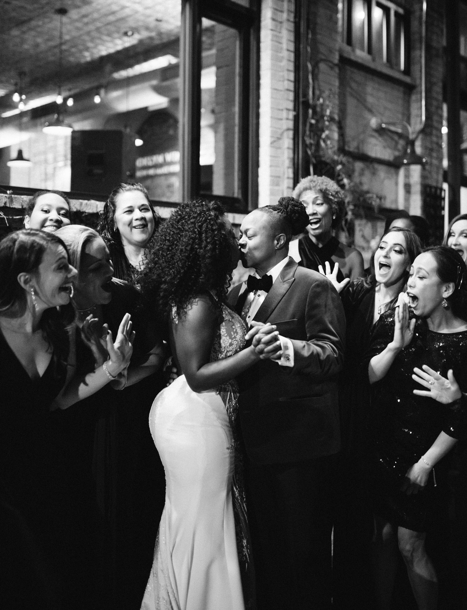 A black lesbian wedding couple is surrounded by cheering and smiling friends as they kiss outside Brooklyn Winery on their winter wedding day in New York City