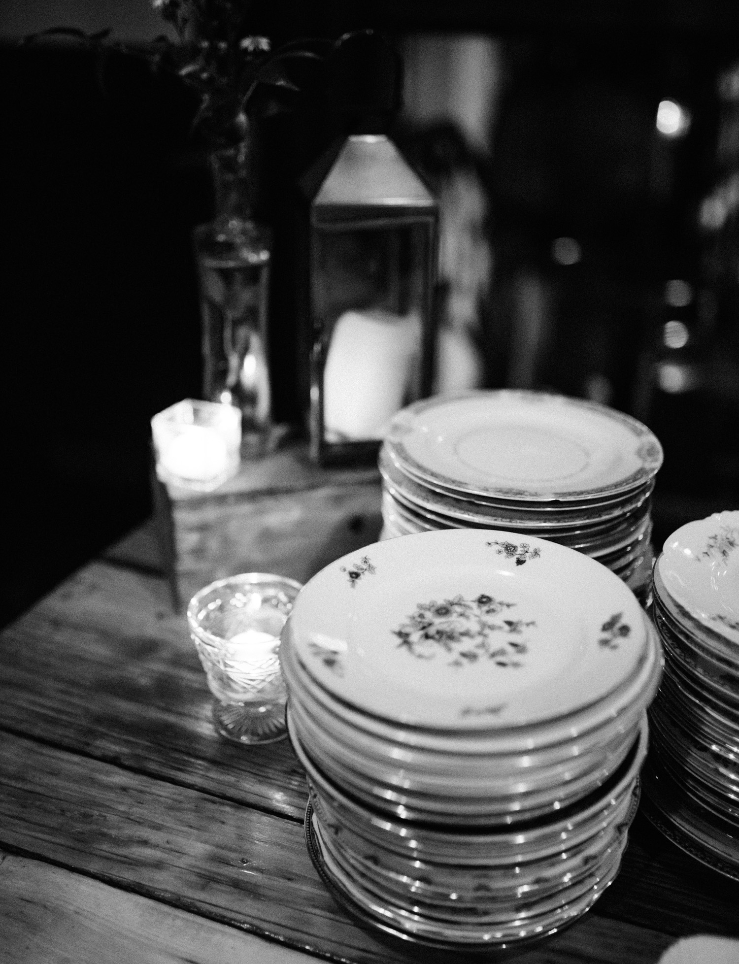 Collected antique plates and candleholders rest on a table during a wedding reception at Brooklyn Winery in New York City