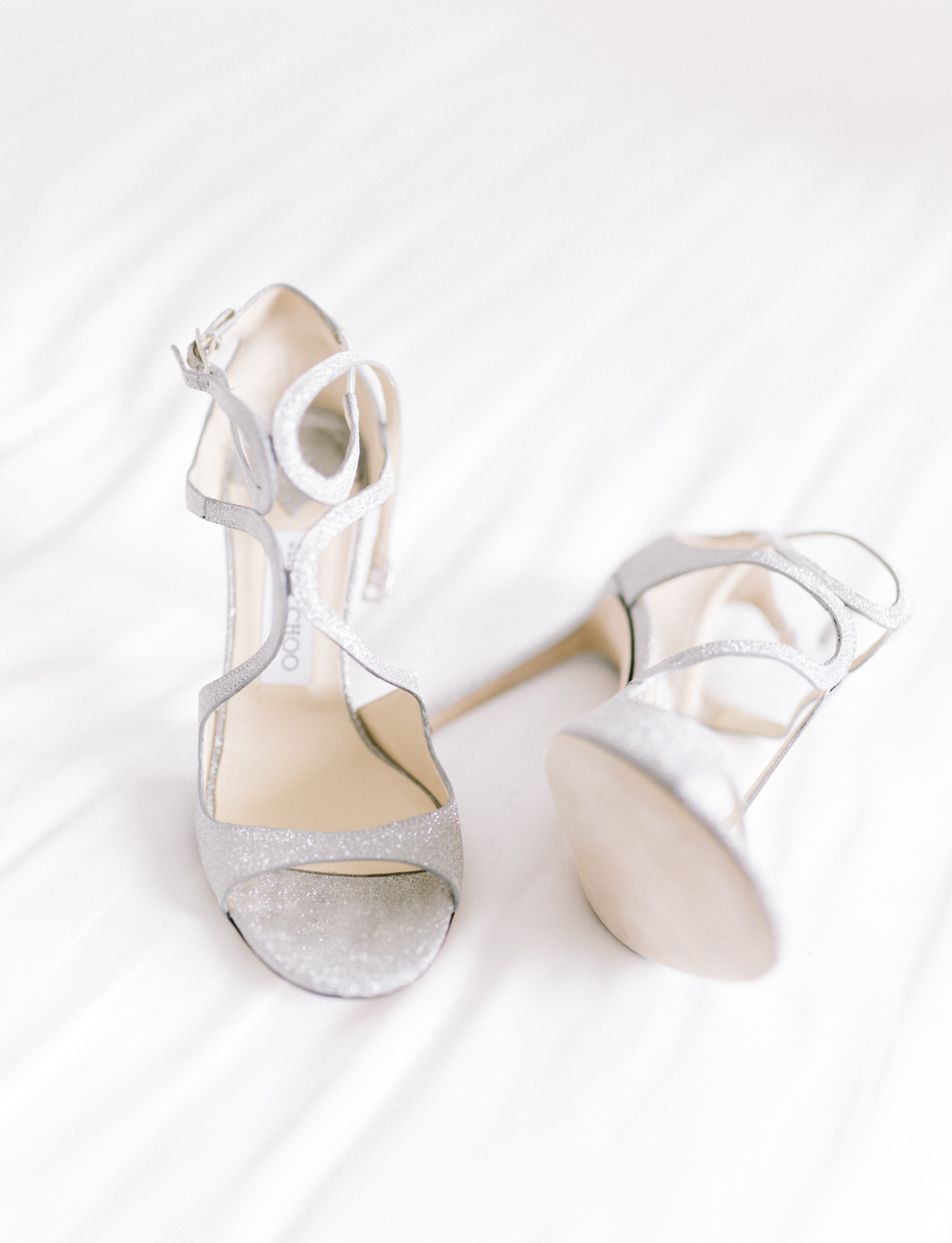 Sparkly silver Jimmy Choo wedding shoes rest on a white hotel bedspread in Brooklyn, New York