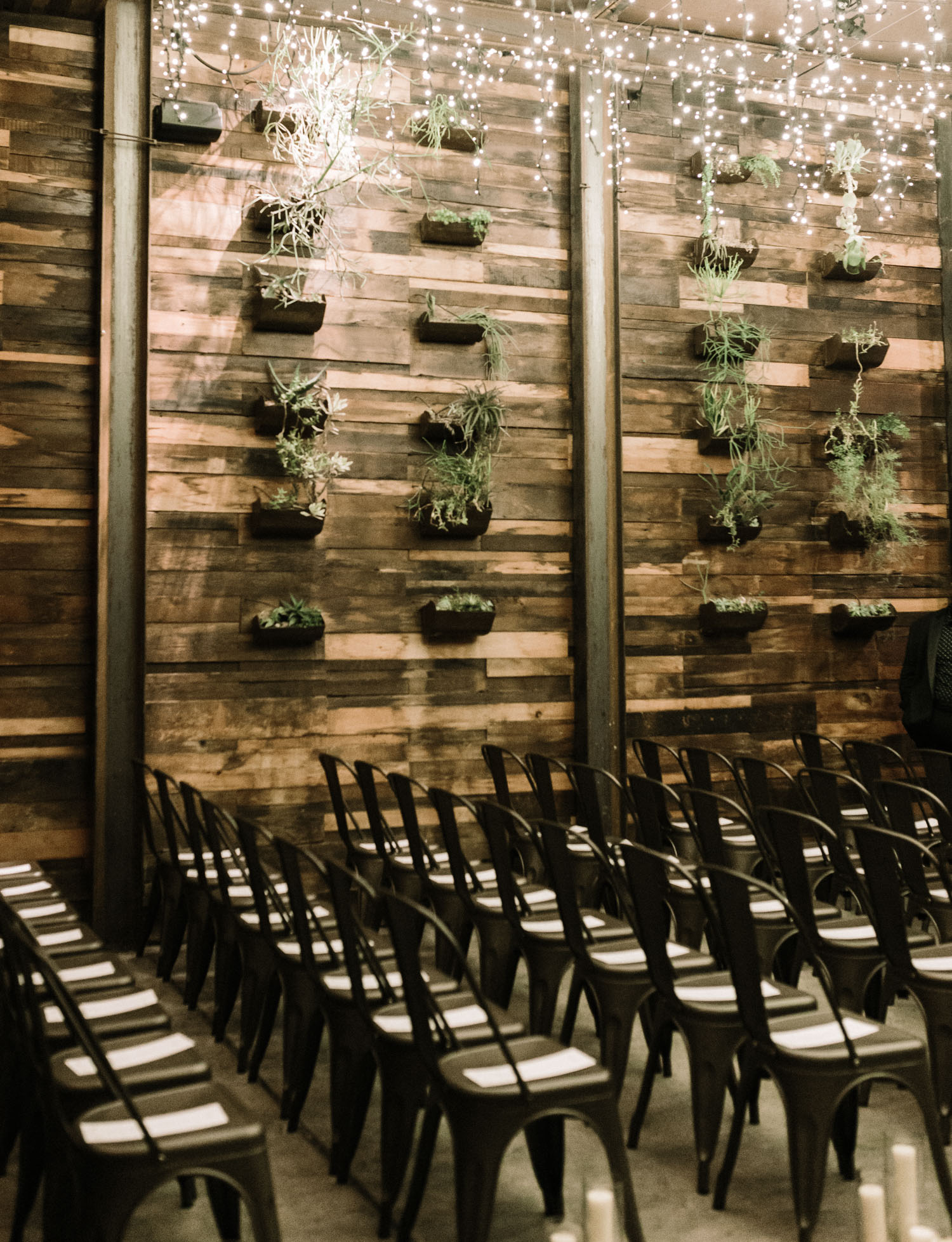 Chairs are set along a succulent wall for a same sex winter wedding ceremony at Brooklyn Winery in New York City