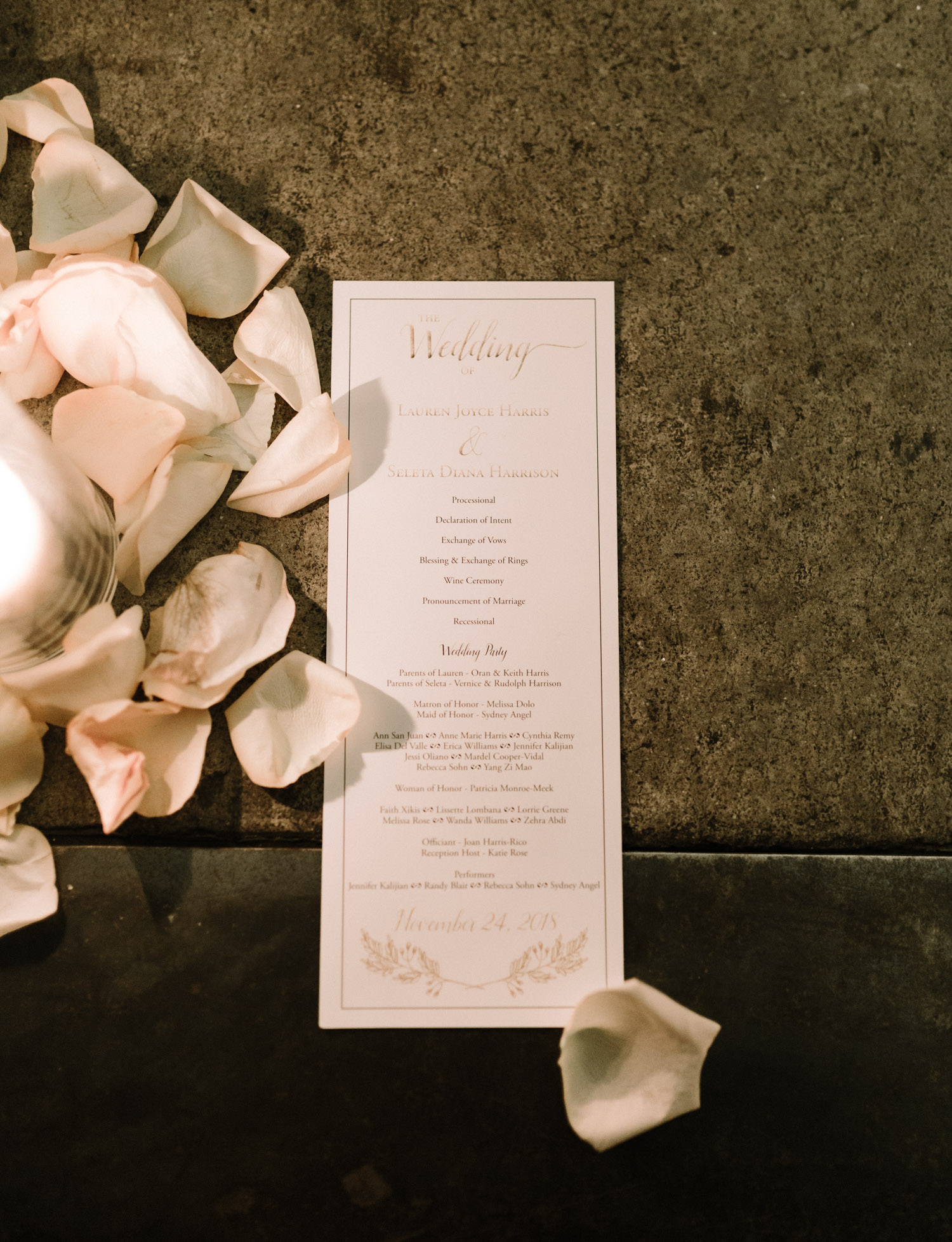 A wedding program rests with candles surrounded by rose petals at Brooklyn Winery in New York City