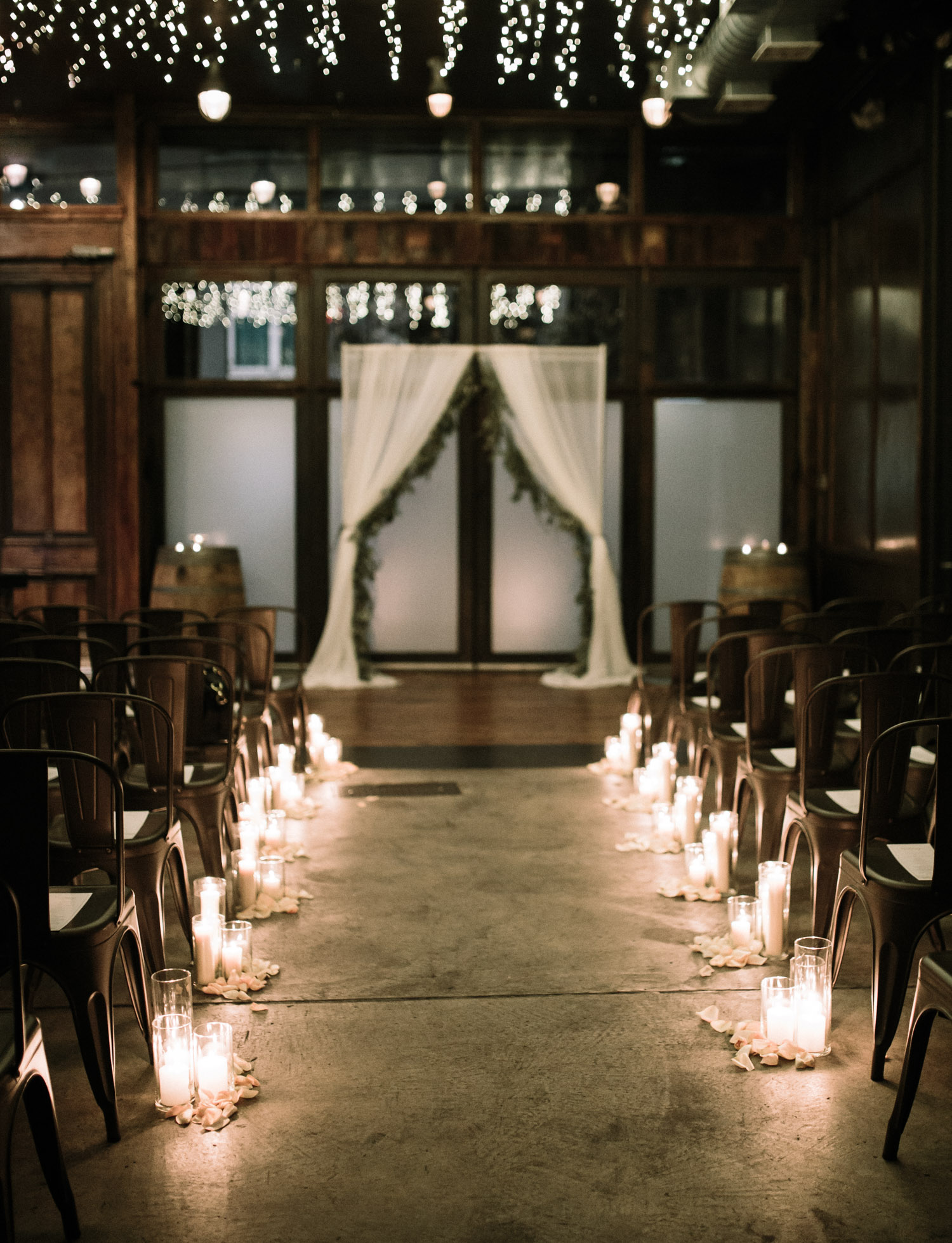 Beautiful candlelit dark winter wedding ceremony decor at Brooklyn Winery, a wedding and reception venue in New York City
