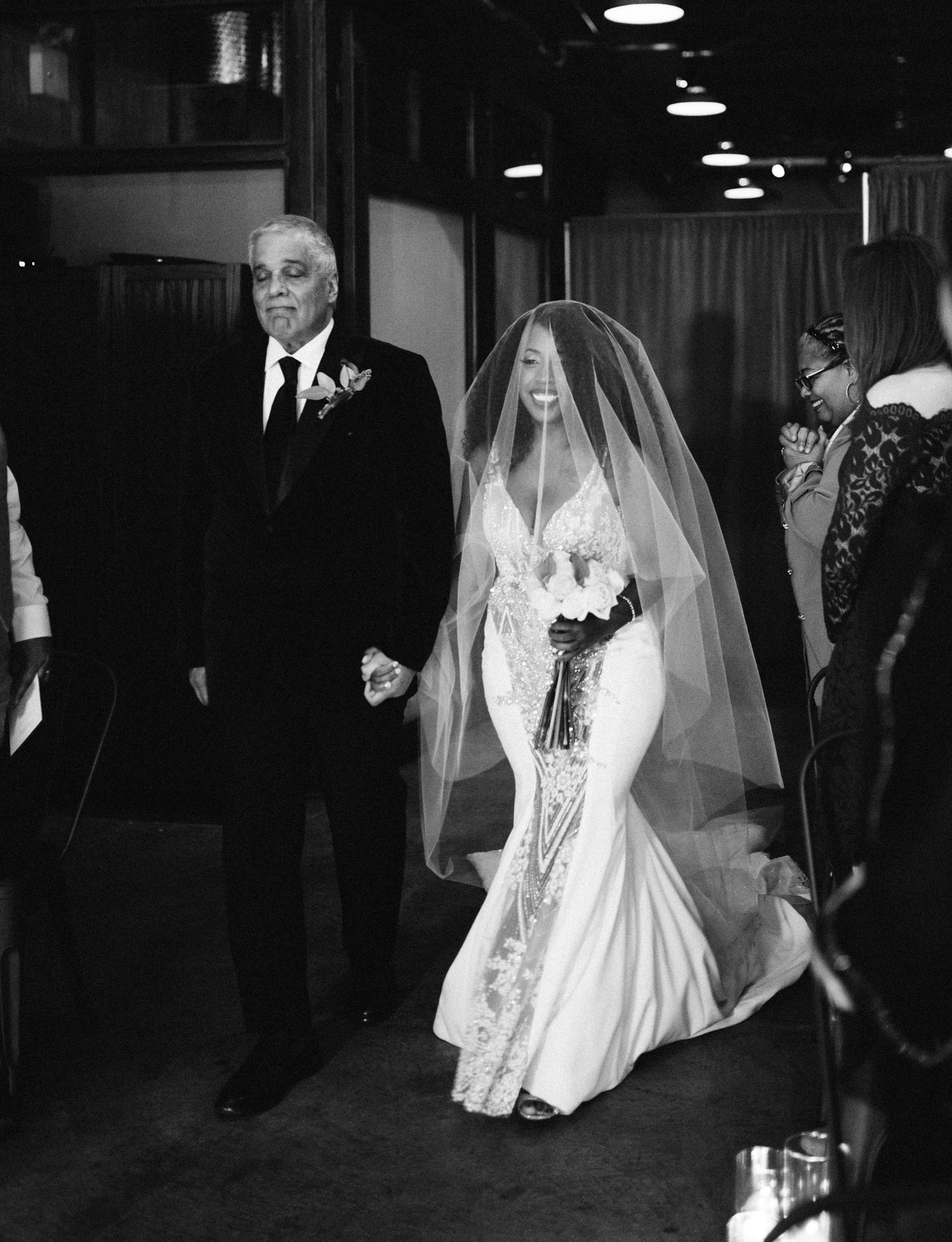 A smiling bride walks down the aisle at Brooklyn Winery with her father